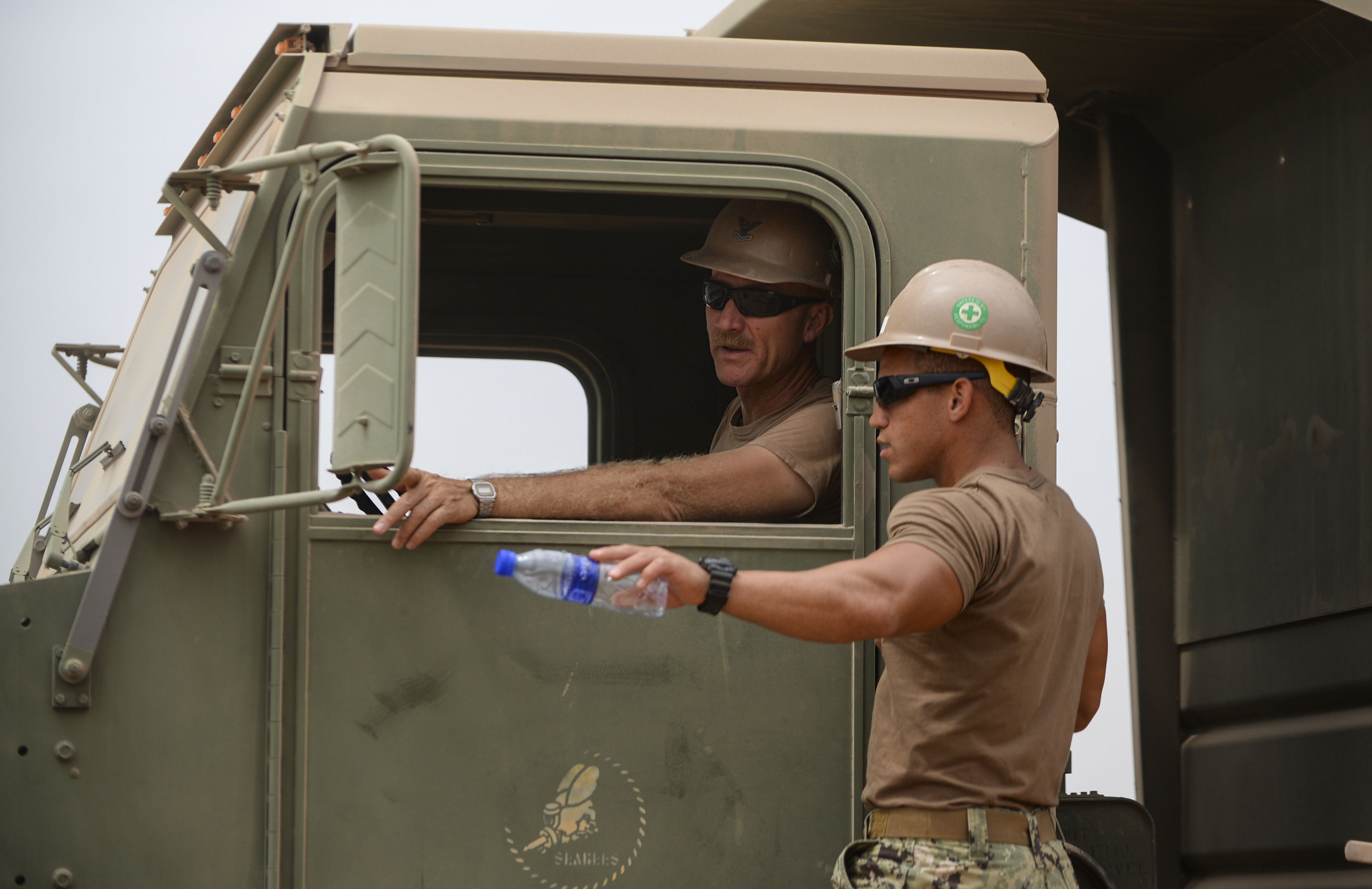 Petty Officer 2nd Class Tom Ross, Naval Mobile Construction Battalion 22 heavy equipment operator, left, talks to Petty Officer 2nd Class Christian Rivera, NMCB 22 heavy equipment operator during construction of a parking pad at a Djibouti airfield, July 28, 2016. During construction, land was flattened, gravel was laid evenly, flattened again and covered with water to increase density and reduce dust. (U.S. Air Force photo by Staff Sgt. Benjamin Raughton/Released)
