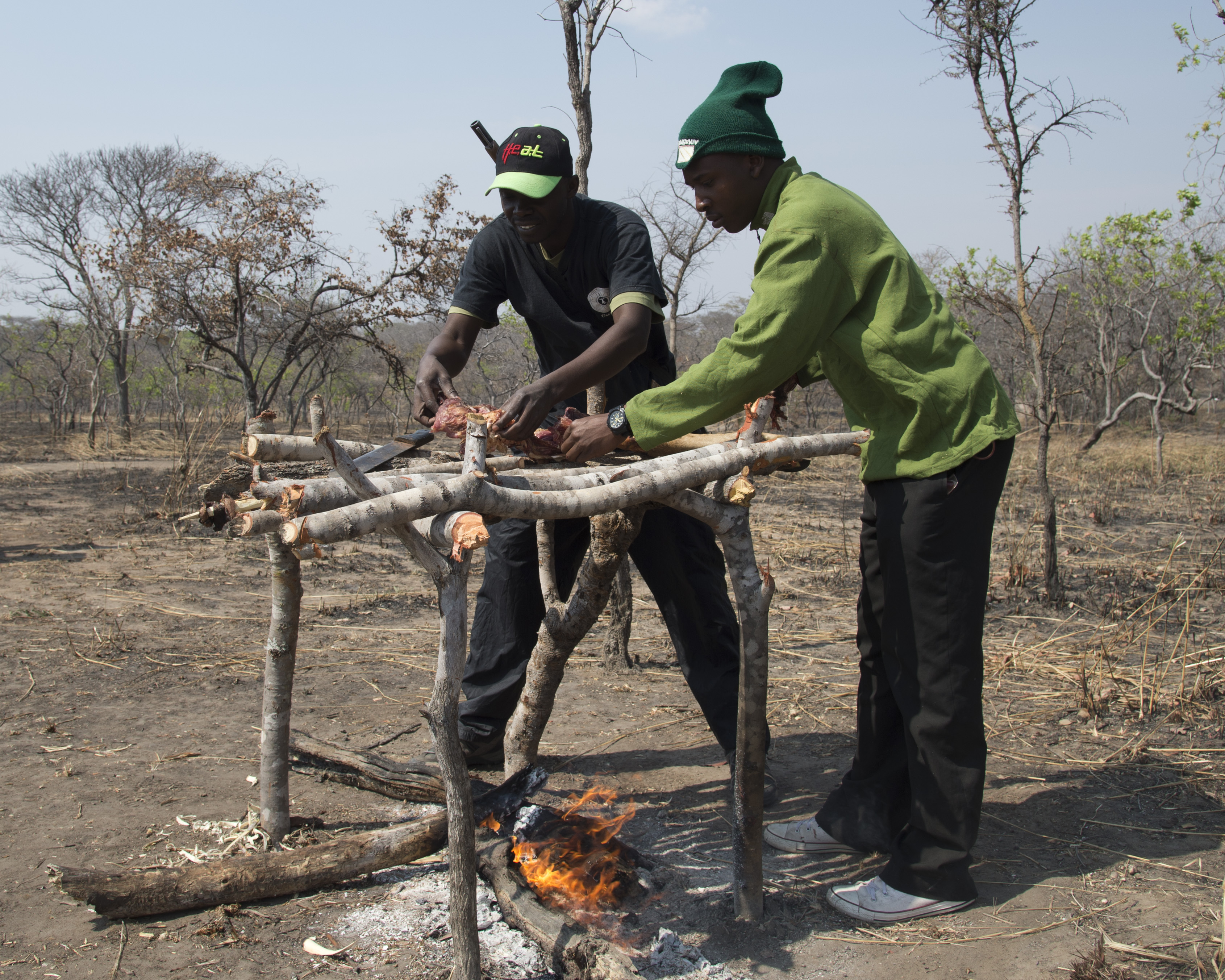 Tanzania park and game reserve rangers, acting as poachers, cook meat from a game reserve animal as part of demonstration August 24, 2016, at Rungwa Game Reserve, Tanzania. The scenario was based around rangers locating a camp of poachers who illegally killed an elephant to harvest its ivory. Rangers recently trained with members of the 403rd Civil Affairs Battalion, a component of Combined Joint Task Force - Horn of Africa, and North Carolina Army National Guard to learn techniques to track and capture poachers. (U.S. Air Force photo by Staff Sgt. Eric Summers Jr.)