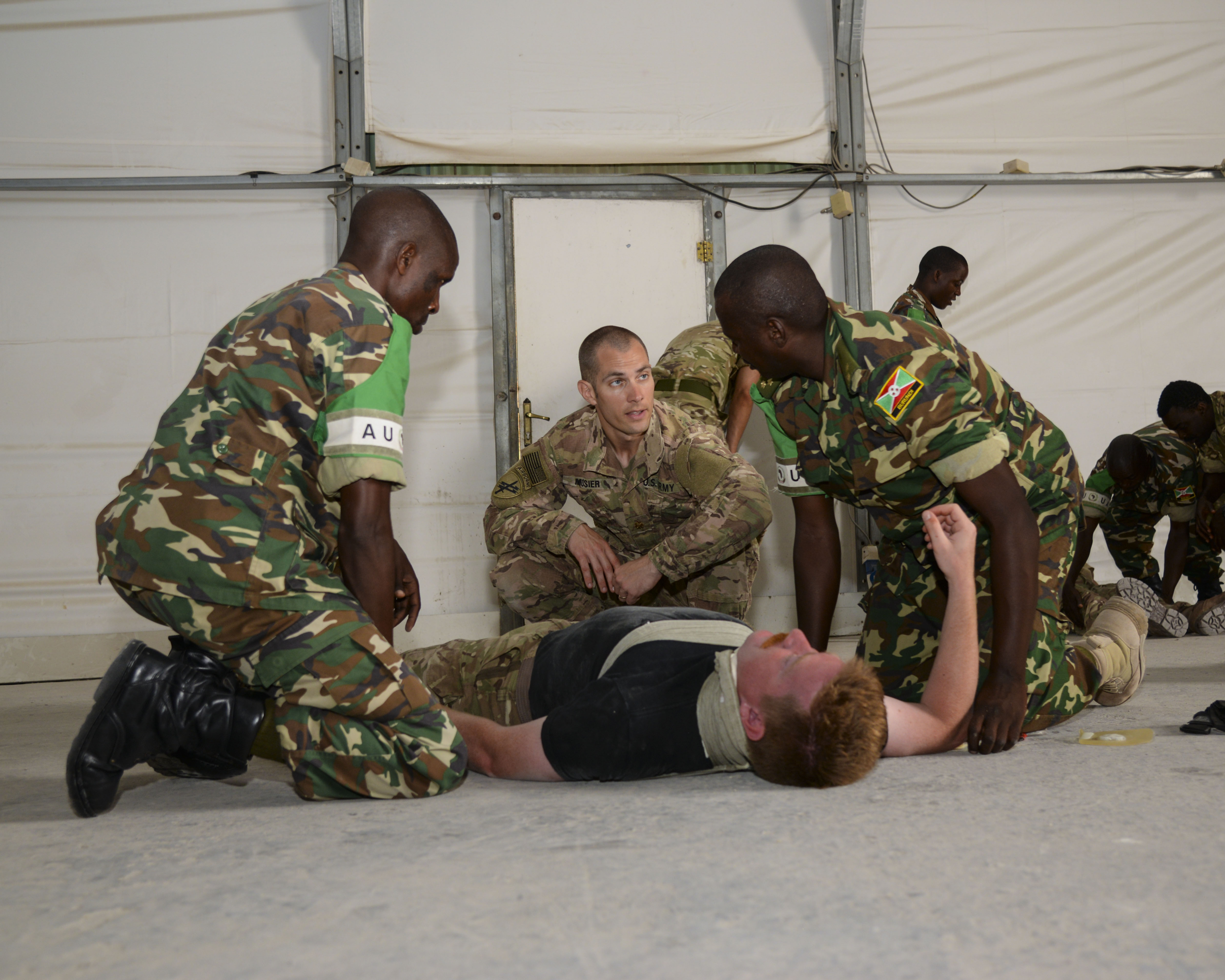 U.S. Army Maj. Andrew Mosier, 403rd Civil Affairs Battalion physician, center, shares medical practices with African Union Mission in Somalia medics during a mass casualty exercise, in Mogadishu, Somalia, Sept. 6, 2016. During the exercise, AMISOM and Somali medics worked as teams to treat life-threatening injuries such as severe blood loss and bullet wounds. (U.S. Air Force photo by Staff Sgt. Benjamin Raughton)