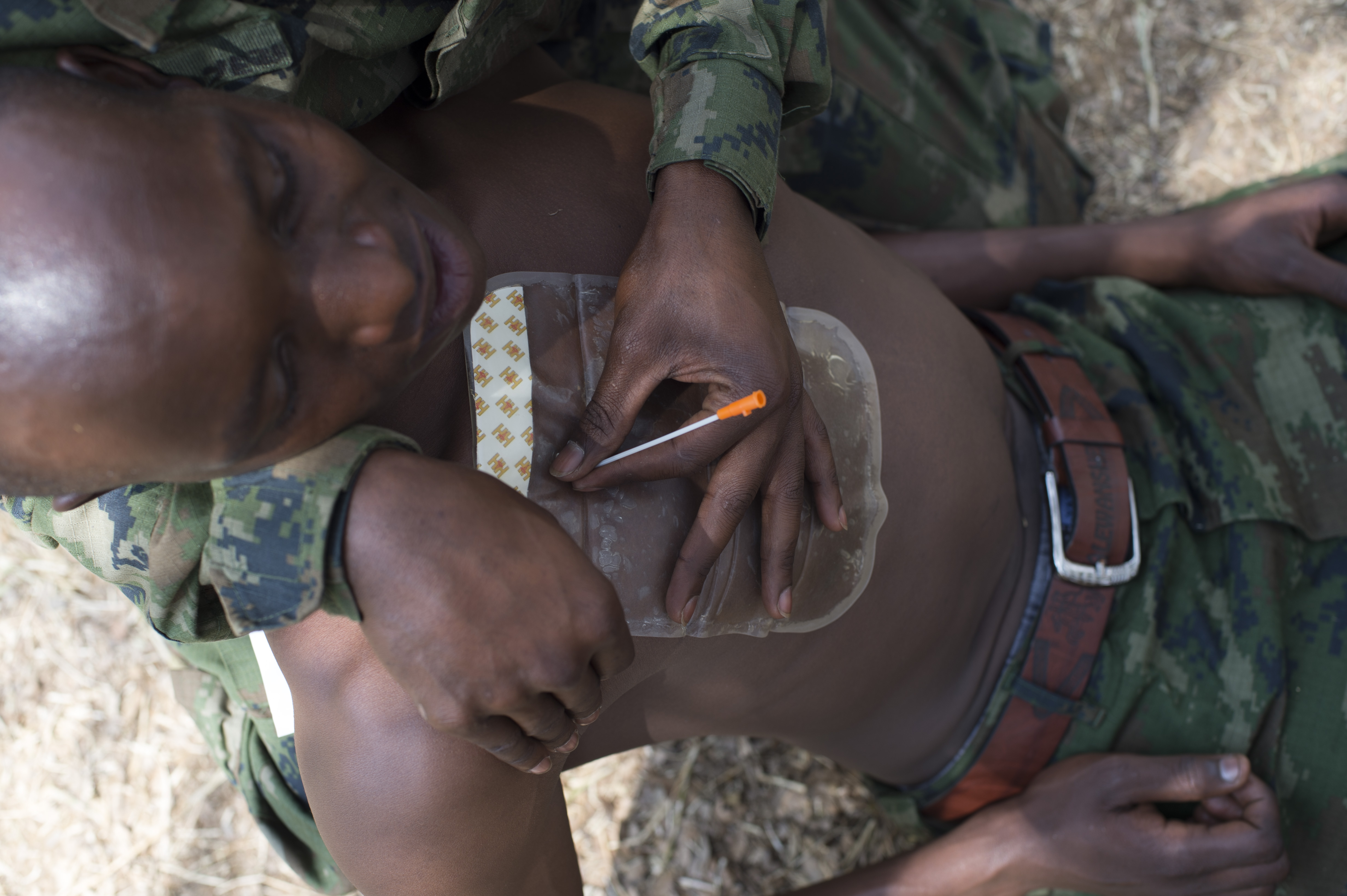 A mock casualty receives a needle chest decompression from a Rwanda Defense Force soldier during a battlefield medical assessment Sept. 8, 2016, at the Rwanda Military Academy, Rwanda. The RDF soldiers participated in a two-week medical course, taught by U.S. Army soldiers deployed to Combined Joint Task Force-Horn of Africa, to learn basic battlefield medical care techniques. (U.S. Air Force photo by Staff Sgt. Eric Summers Jr.)