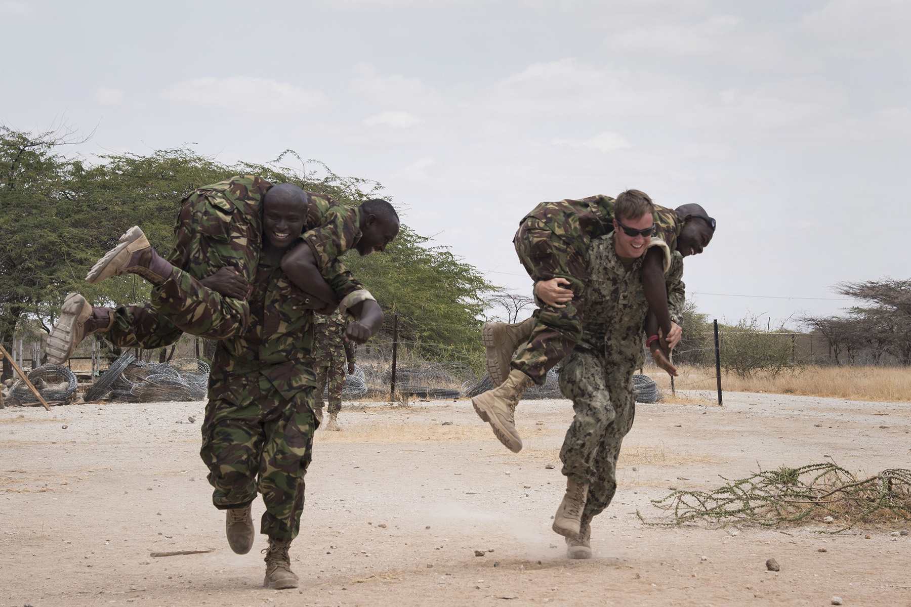 KENYA- U.S. Navy Explosive Ordnance Disposal Technician 3rd Class Nick Mettler, assigned to Task Force Sparta and currently deployed to Combined Joint Task Force-Horn of Africa, races Kenyan Defense Force combat engineers during a buddy carry lesson for the tactical combat medical training portion of Deliberate Kindle 2016, Sept. 14, at a Kenyan training facility. The medical training was just one portion of the four-week course designed to give Humanitarian Mine Action training to course attendees to prepare them for future deployments with the African Union Mission in Somalia. (U.S. Air Force photo by Staff Sgt. Tiffany DeNault)