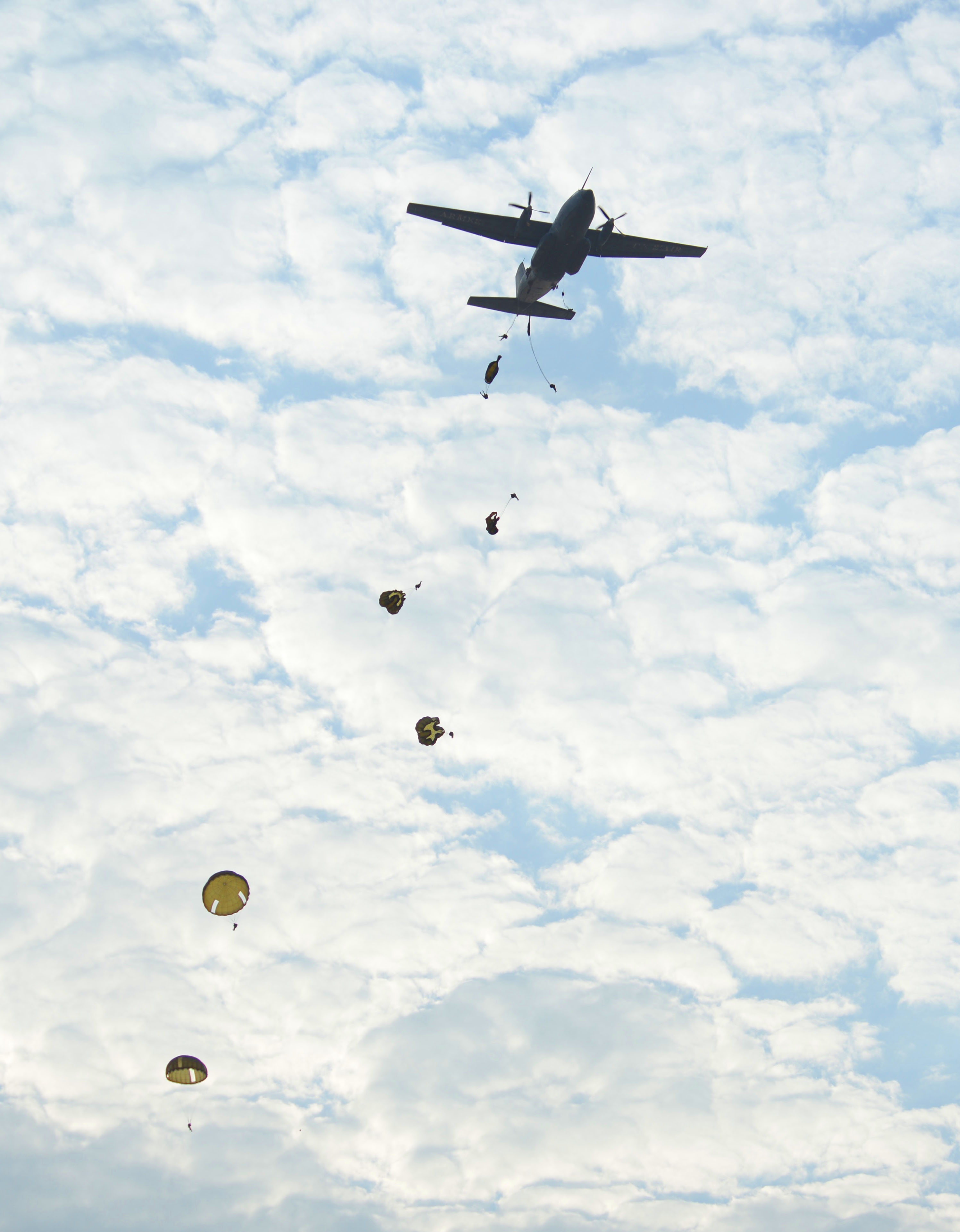 Military members from the U.S. Army, Djibouti Armed Forces, and French military kick off a St. Michel's Day celebration by jumping out of a C-160 Transall in Djibouti, Sept. 29, 2016. The paratroopers commemorated the day with a static line and high altitude low opening jump toward a designated drop zone. (U.S. Air Force photo by Staff Sgt. Benjamin Raughton)