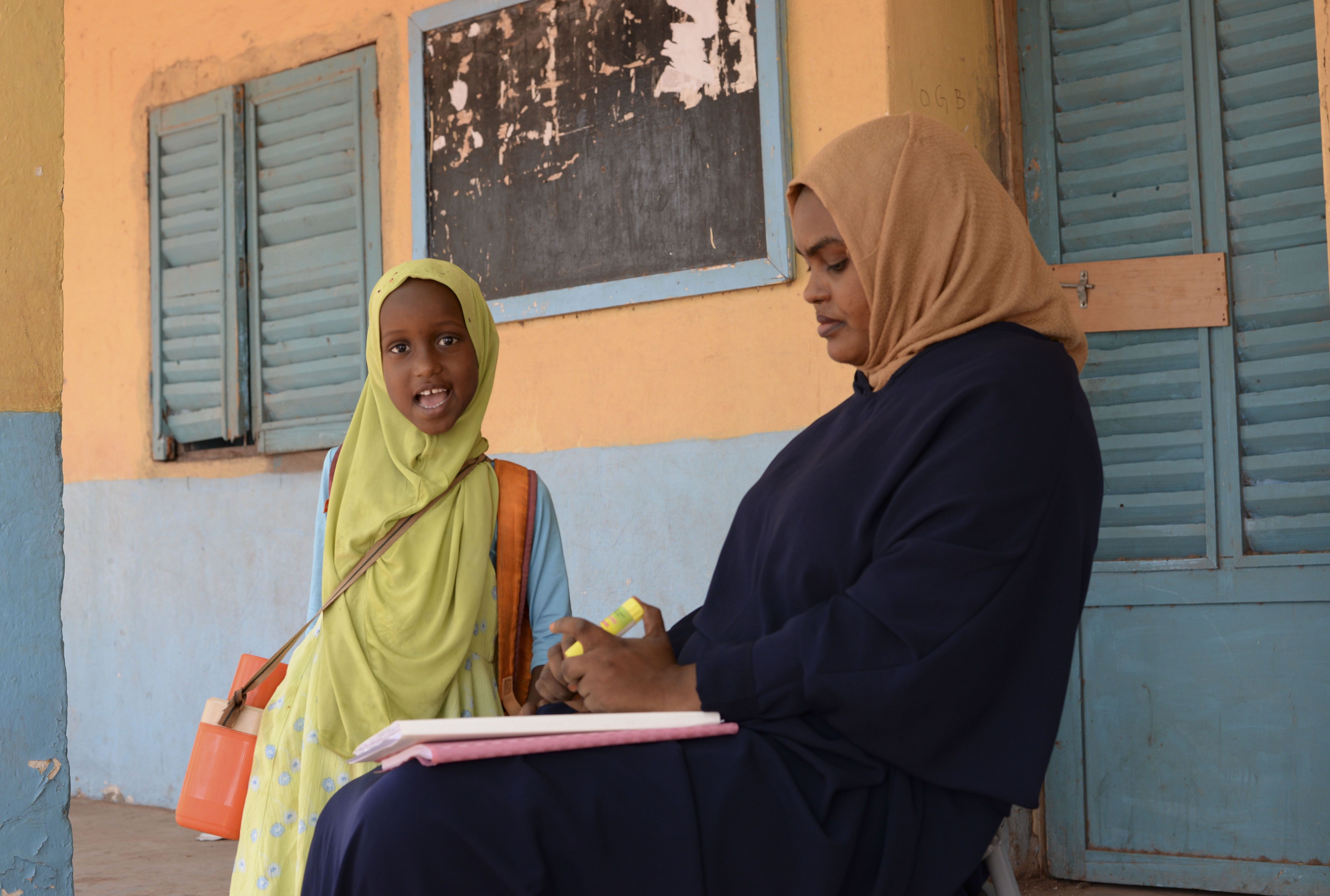 A student and her mother work on lessons together outside a school in Dikhil, Djibouti, Sept. 27, 2016. A new schoolhouse addition is scheduled to open later this year that will provide additional classrooms to accommodate a growing Dikhil population and local nomadic tribes that also send their children to Dikhil schools. (U.S. Air Force photo by Staff Sgt. Benjamin Raughton)