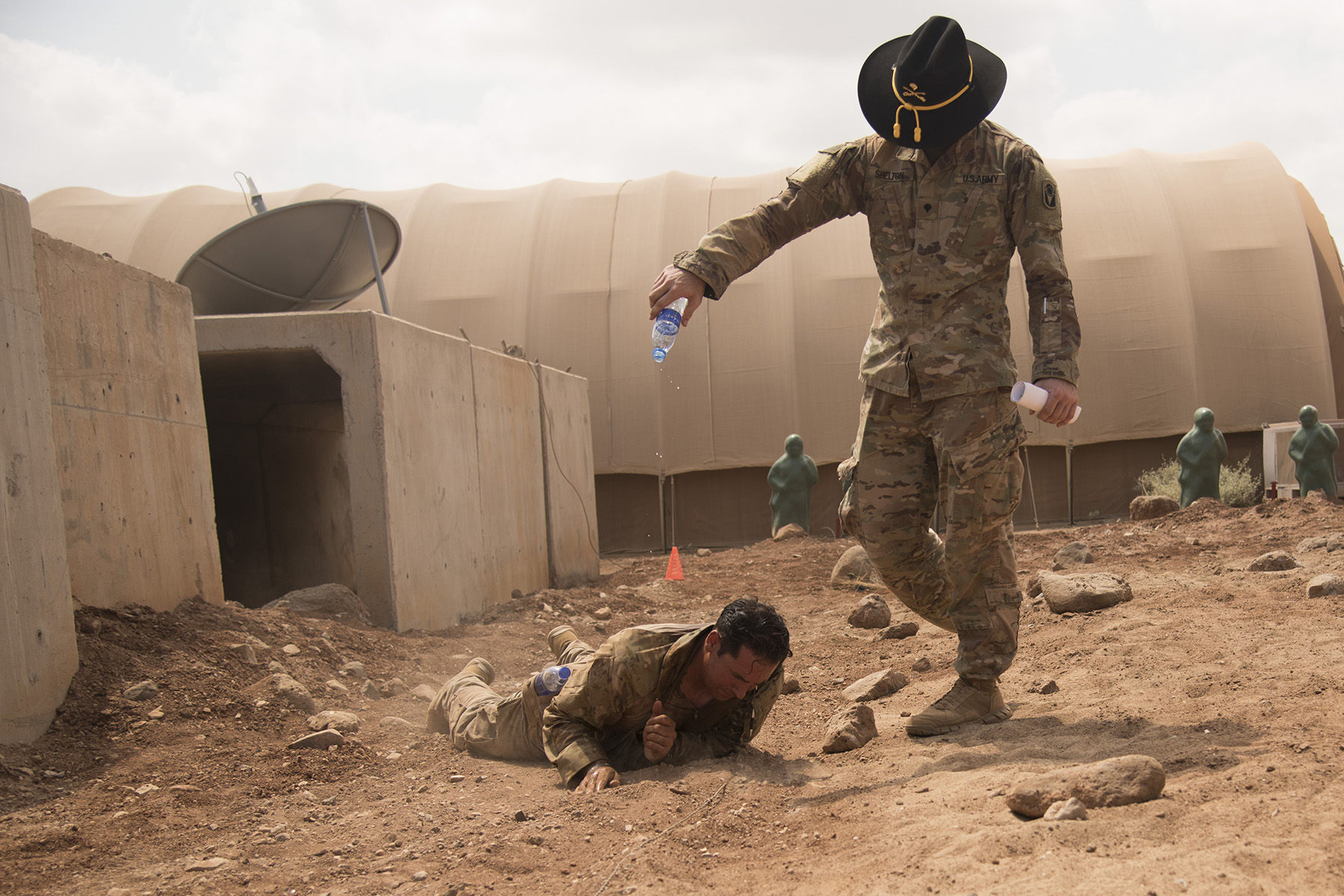 DJIBOUTI- U.S. Army Spc. Joe Shelton, pours water on Sgt. 1st Class Samuel Amador, 1st Battalion, 124th Infantry Regiment, while he hides a wire after securing a mock claymore mine during a spur ride event, Oct. 21, 2016, at a nearby airfield in Djibouti. Twenty-eight U.S. Army Soldiers and one Air Force Airman participated in the traditional Army event where they completed 10 tasks with various stress events before each task in approximately 19 hours. (U.S. Air Force photo by Staff Sgt. Tiffany DeNault)