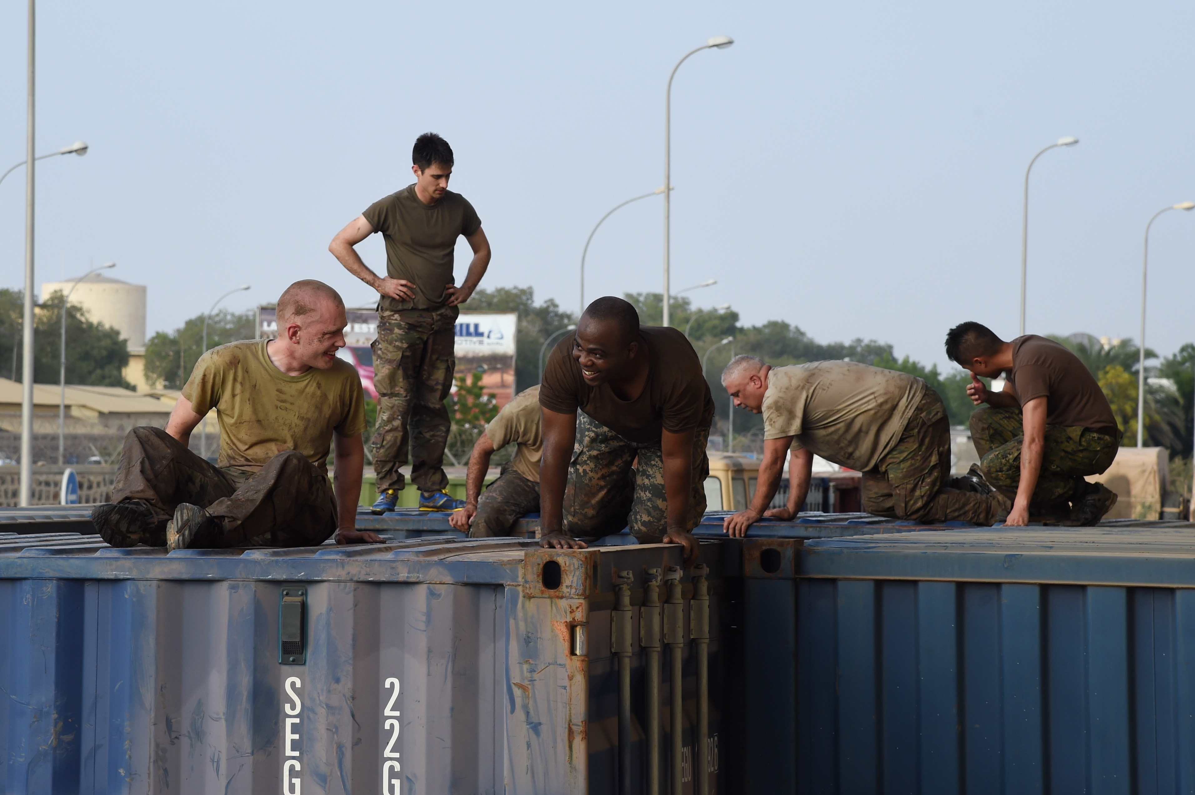 Service members from Combined Joint Task Force-Horn of Africa Civil Affairs climb over obstacles during a mud run hosted by the French military, Nov. 6, 2016, in Djibouti, Djibouti. The event allowed coalition forces from French, Japanese, and American teams to interact and build camaraderie while navigating a five kilometer course. The French 5th Marine Regiment team took first place. (U.S. Air Force photo by Staff Sgt. Penny Snoozy)