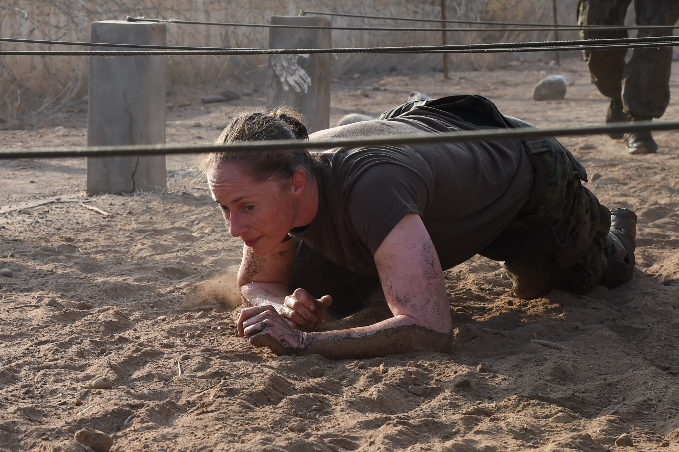 U.S. Navy Lt. Cmdr. Brighid Clark, Combined Joint Task Force-Horn of Africa Civil Affairs, navigates a low-crawl obstacle during a mud run hosted by the French military, Nov. 6, 2016, in Djibouti, Djibouti. The event allowed coalition forces from French, Japanese, and American teams to interact and build camaraderie while navigating a five kilometer course. The French 5th Marine Regiment team took first place. (U.S. Air Force photo by Staff Sgt. Penny Snoozy)