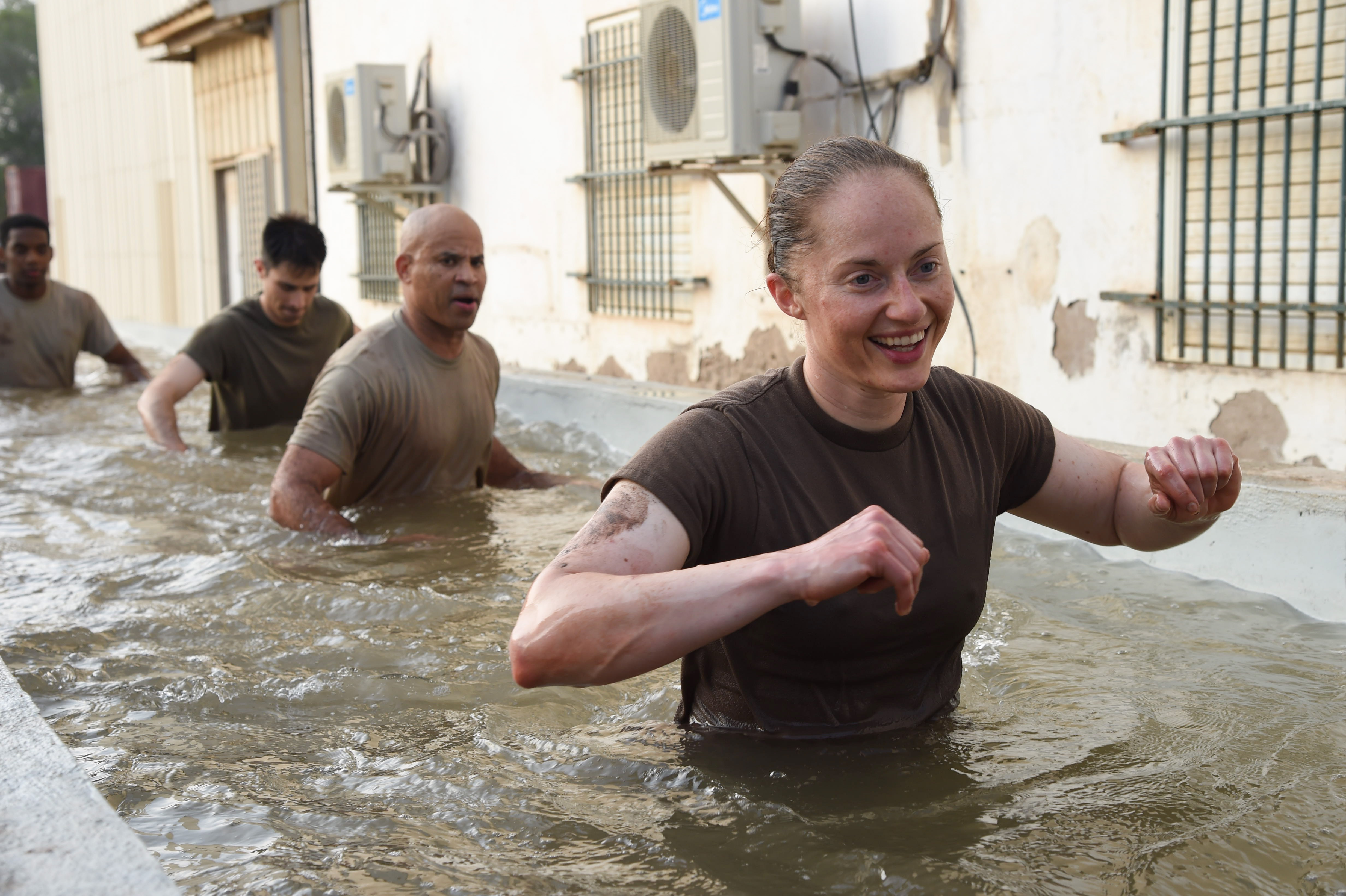 U.S. Navy Lt. Cmdr. Brighid Clark, Combined Joint Task Force-Horn of Africa Civil Affairs, wades through the resistance pool obstacle during a mud run hosted by the French military, Nov. 6, 2016, in Djibouti, Djibouti. The event allowed coalition forces from French, Japanese, and American teams to interact and build camaraderie while navigating a five kilometer course. The French 5th Marine Regiment team took first place. (U.S. Air Force photo by Staff Sgt. Penny Snoozy)