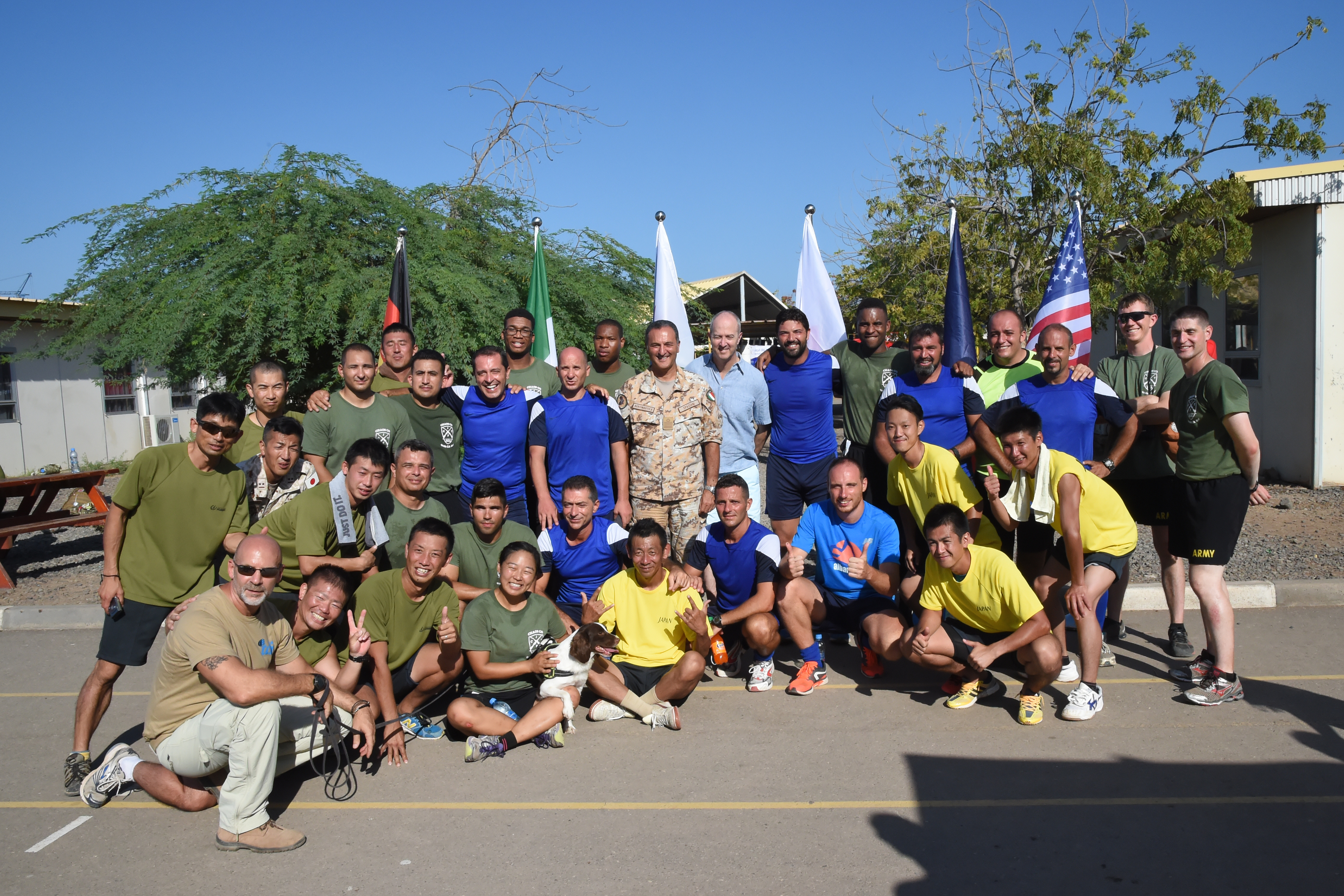 Soccer players representing military units from Italy, Japan and the U.S. are joined by U.S. Ambassador to Djibouti Tom Kelly during a tournament at the French school Kessel in downtown Djibouti Dec. 9, 2016. The event brought together eleven different teams from six countries for friendly competition in support of the Kick for Nick Foundation. (U.S. Air National Guard photo by Master Sgt. Paul Gorman)