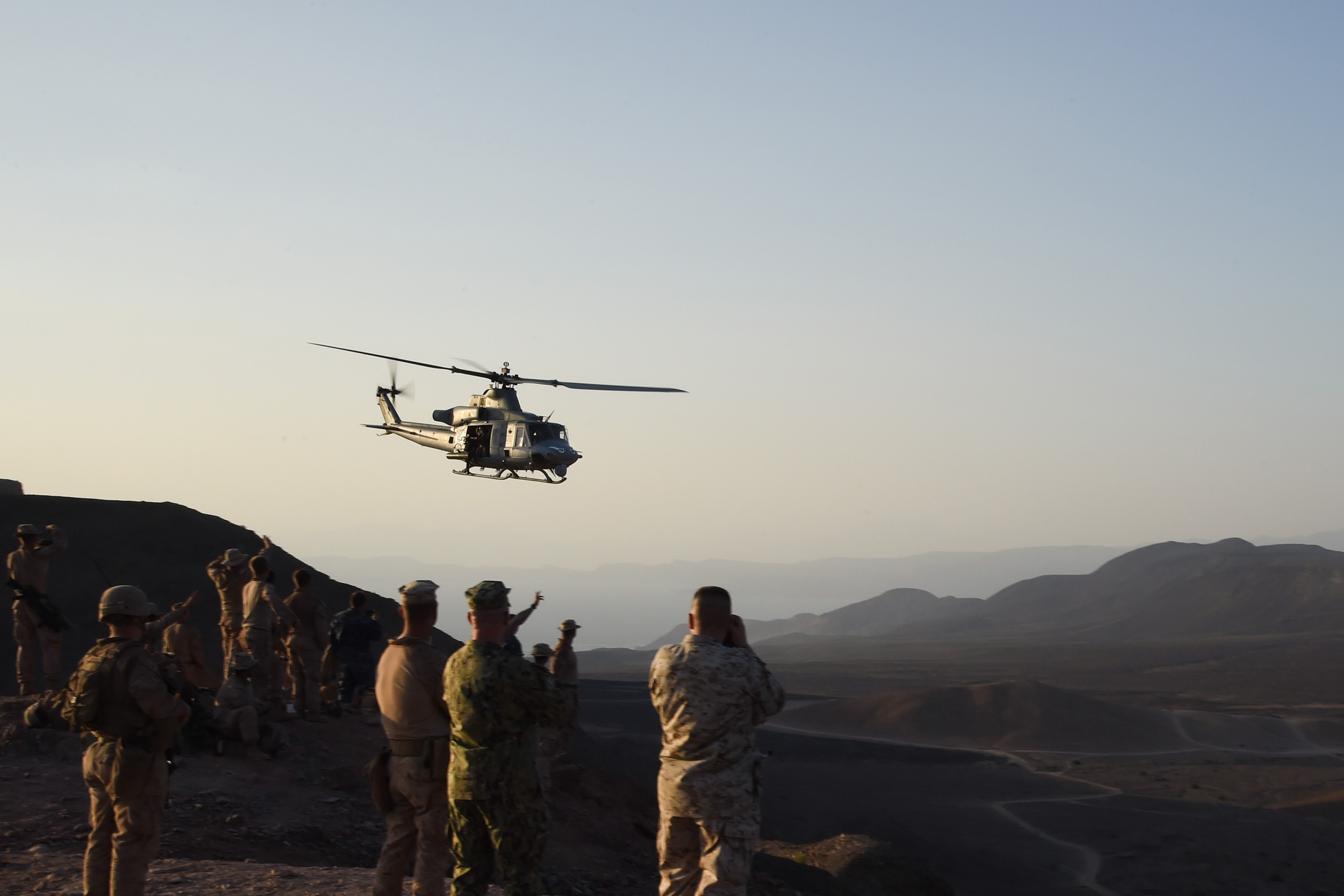 U.S. Marine Corps members with the11th Marine Expeditionary Unit (MEU), and Sailors from the Makin Island Amphibious Ready Group, watch an UH-1Y Huey helicopter fly over after a helo-borne raid on the range during Exercise Alligator Dagger, Dec. 18, 2016, at Arta Plage, Djibouti. The exercise allows opportunities for the 11th MEU to maintain their respective skills and proficiencies while intermittently participating in bilateral training with the French. (U.S. Air National Guard photo by Staff Sgt. Penny Snoozy)