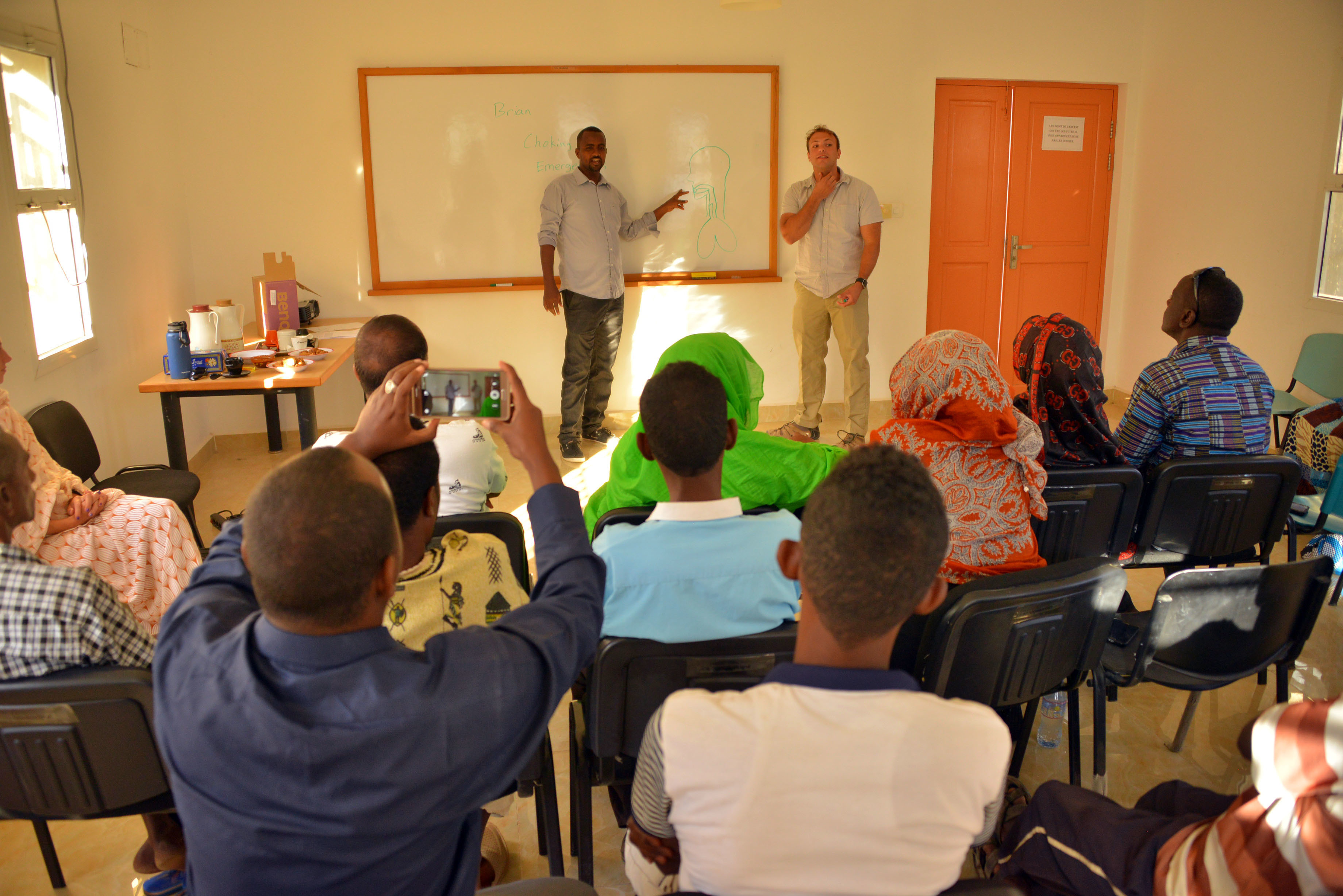 SOS Village D' Enfants – Tadjoura administrators, staff members, and caretakers record footage and listen to a discussion on airway blockage given by Sgt. Brian Duckworth, a civil affairs team medic with C/Co 411th Civil Affairs Battalion, here on January 3, 2017. The SOS Village provides cares for 90 Djiboutian children at its compound and partnered with a local civil affairs team to hold discussions in shared best practices related to administering first aid.                                                                                                                  (US Army Photo By: Staff Sgt. Gregory Williams C Co/411th Civil Affairs Battalion)