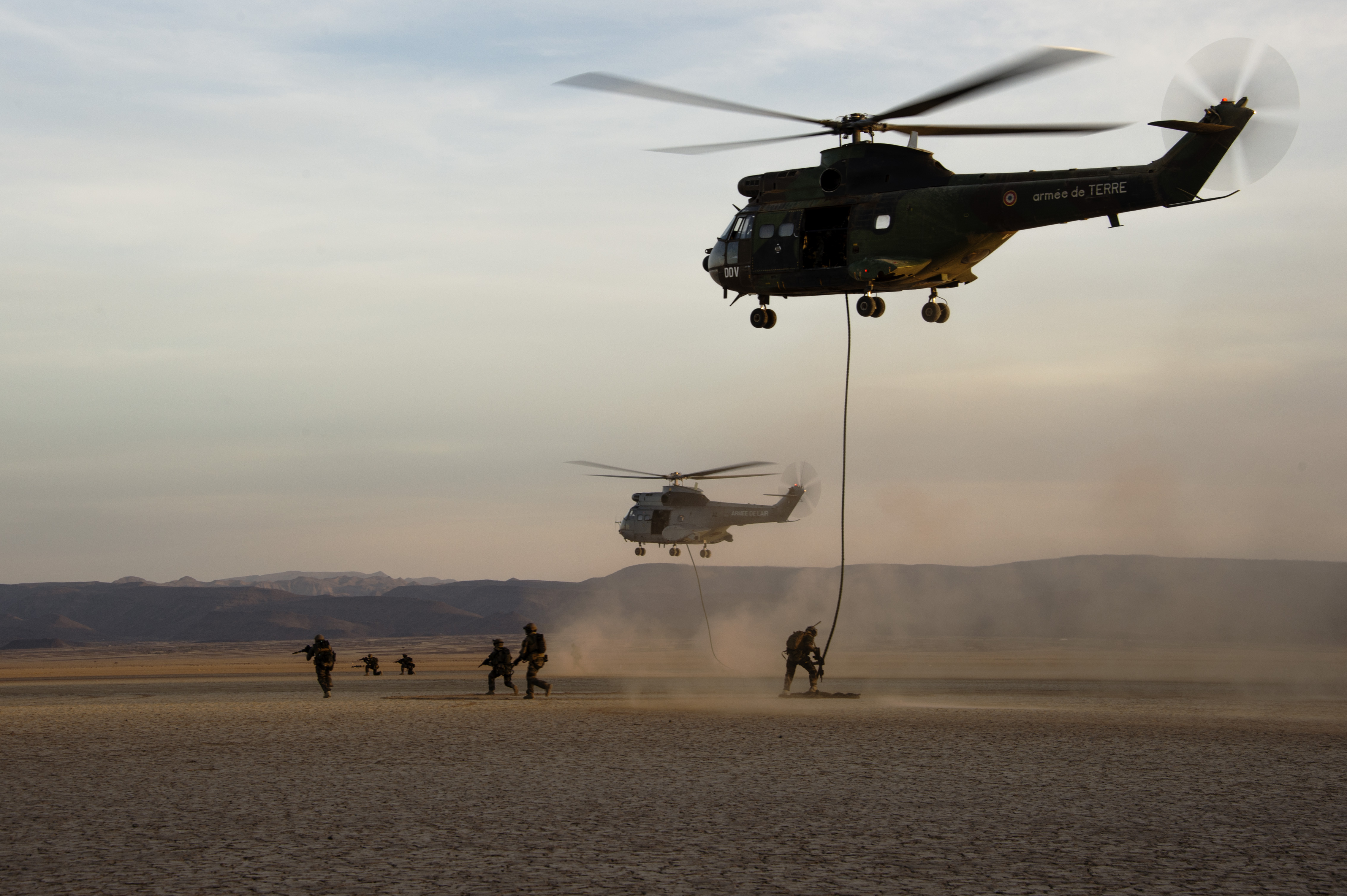 French military members repel out of two SA 330 Puma transport helicopters to secure a landing site during the French live fire demonstration near Grand Bara, Djibouti, Jan. 14, 2017. The SA 330 Puma is a medium lift, all-weather helicopter capable of transporting up to 16 people in and out of a battlefield. (U.S. Air National Guard photo by:  Staff Sgt. Christian Jadot)