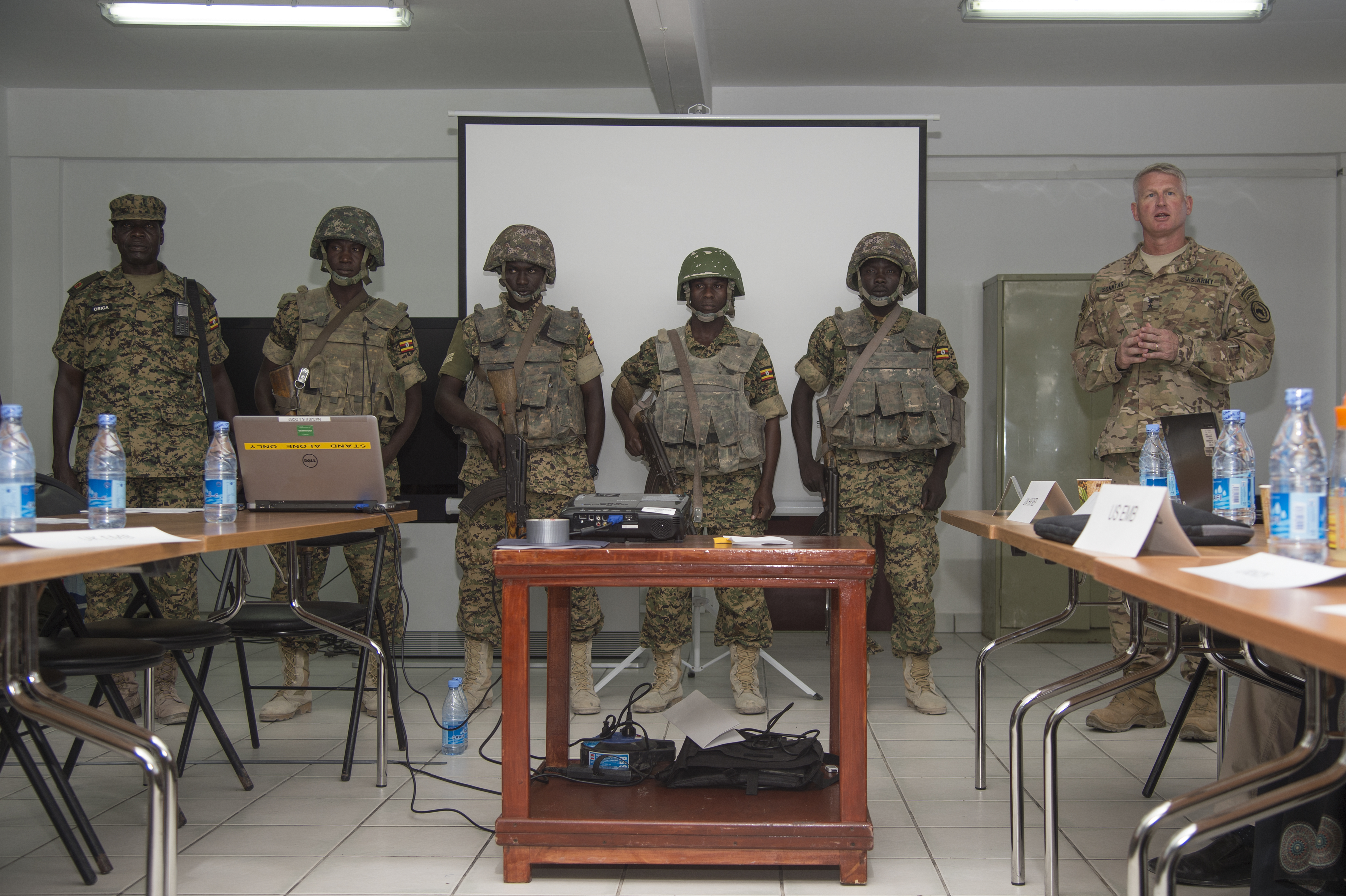 Maj. Gen. Kurt Sonntag, commanding general of the Combined Joint Task Force-Horn of Africa, right, recognizes members of the Ugandan military responsible for defeating a vehicle borne IED attack while serving with the African Union Mission in Somalia during the SNA Symposium in downtown Mogadishu, Jan. 11, 2017. AMISOM is an active, regional peacekeeping mission operated by the African Union with the approval of the United Nations in Somalia.