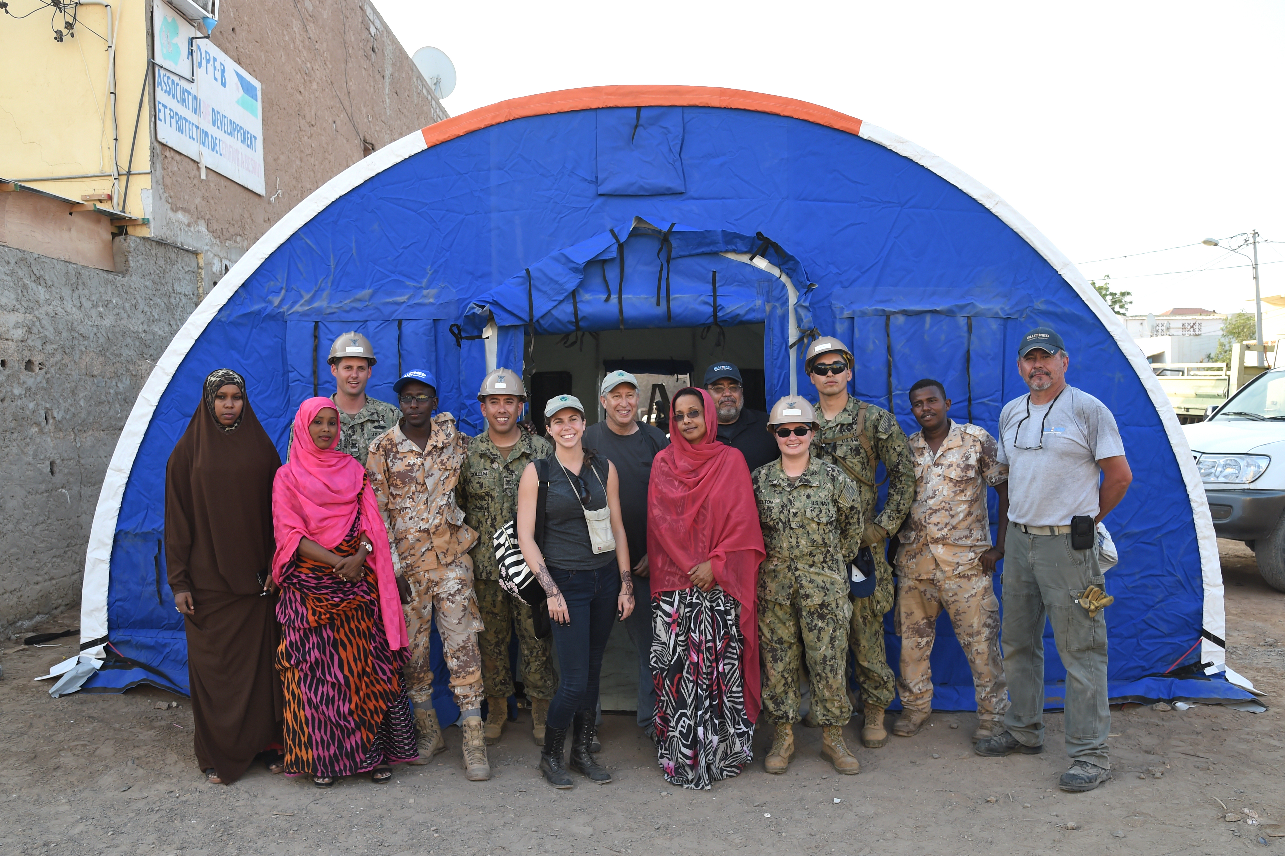 U.S. Navy Seabees with Naval Mobile Construction Battalion 1, join Djibouti Armed Forces soldiers, and representatives from Alaska Shelters, the Global Action Coalition and the Association for the Development and Protection of Children (ADPEB) following the construction of a modular shelter system in Djibouti City, Feb. 27, 2017. The shelter is one of six donated by Alaska Shelters through the Global Action Coalition, and will give the ADPEB additional shelter and classroom space for homeless children in Djibouti. (U.S. Air National Guard photo by Master Sgt. Paul Gorman)
