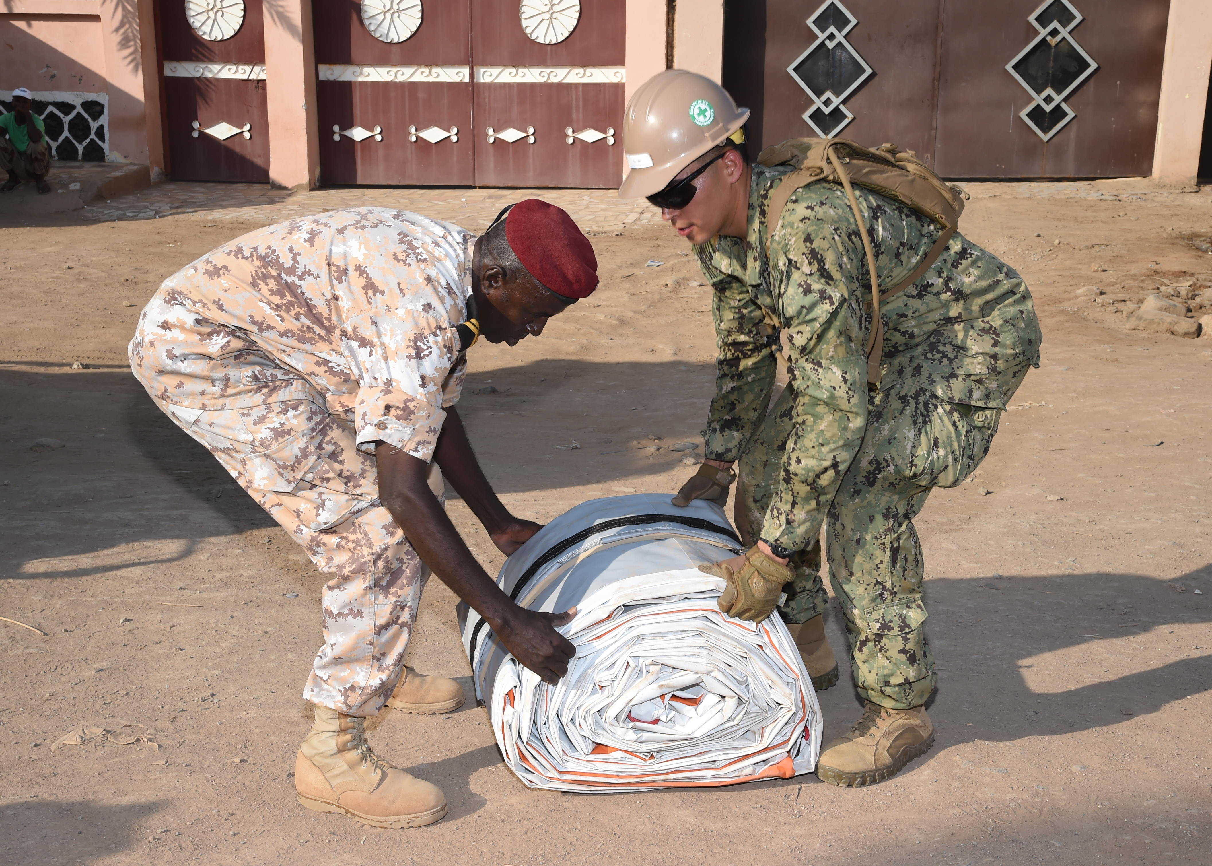 U.S. Navy Hospital Corpsman 3rd Class David Rojas, a Seabee with Naval Mobile Construction Battalion 1, exercises teamwork with a Djibouti Armed Forces soldier during the construction a modular shelter system in Djibouti City, Feb. 27, 2017. The shelter is one of six donated by U.S. manufacturer Alaska Shelters through the Global Action Coalition, for to use as schools, clinics, and centers for cottage industry to promote the health, education and economic stability of the Djiboutian people. (U.S. Air National Guard photo by Master Sgt. Paul Gorman)