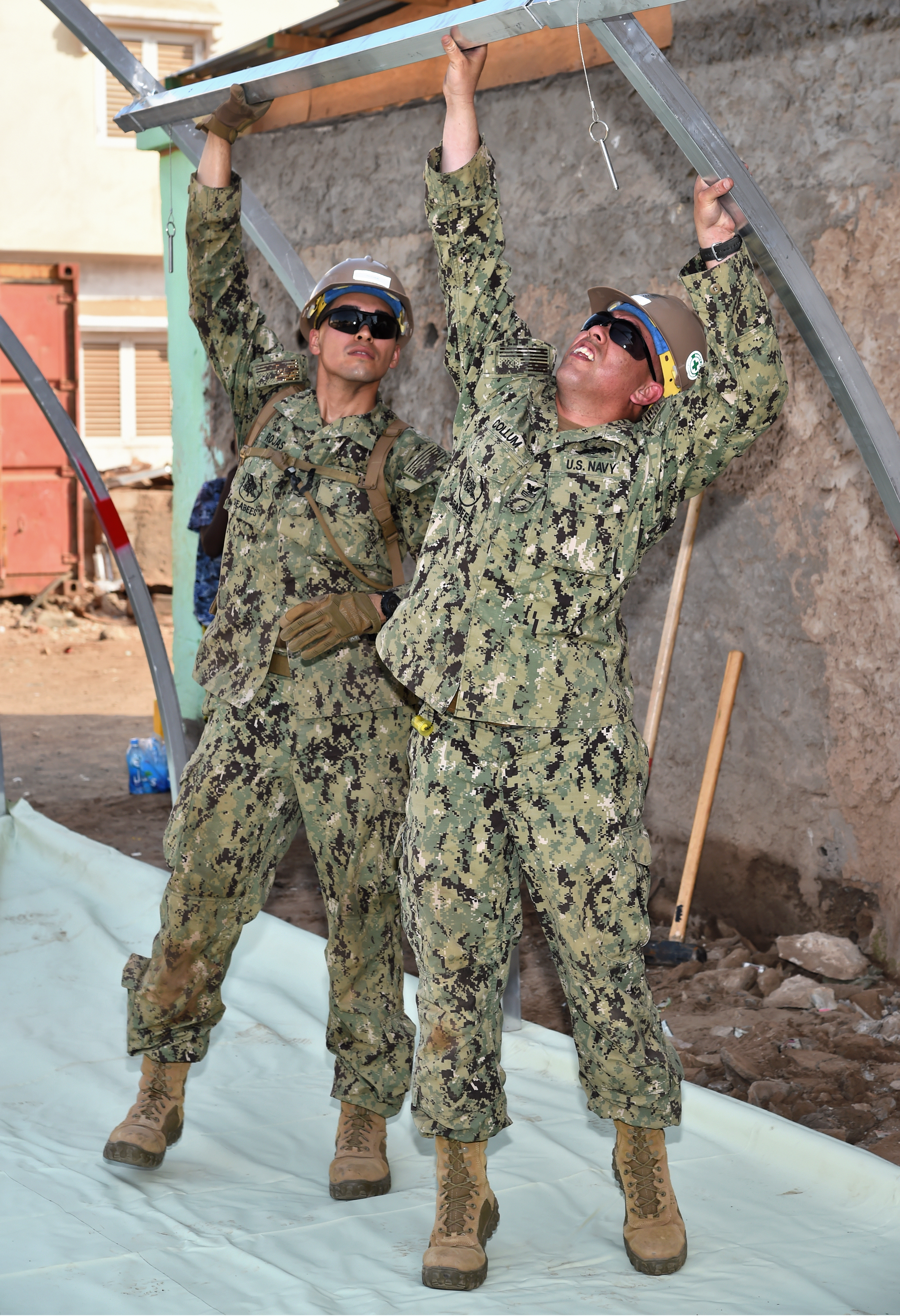 U.S. Navy Steelworker 1st Class Michael Collum, right, and Hospital Corpsman 3rd Class David Rojas, Seabees with Naval Mobile Construction Battalion 1, help to construct a modular shelter system in Djibouti City, Feb. 27, 2017. The shelter is one of six donated by U.S. manufacturer Alaska Shelters through the Global Action Coalition, and will provide additional classroom space for the Association for the Development and Protection of Children in downtown Djibouti. (U.S. Air National Guard photo by Master Sgt. Paul Gorman)