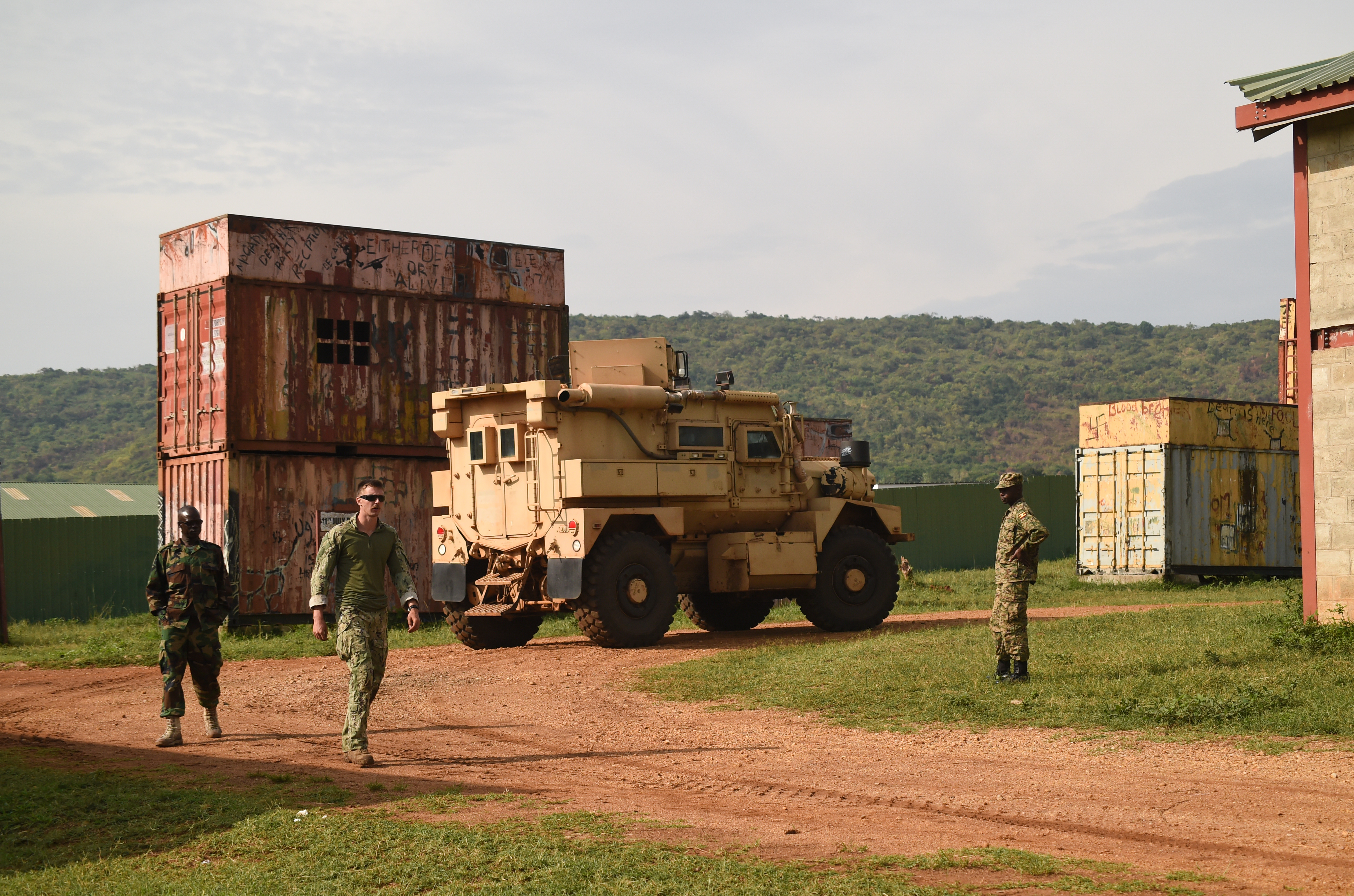 U.S. Navy Explosive Ordnance Disposal Technician 2nd Class Gary Lathrop, Combined Joint Task Force-Horn of Africa, Task Force Sparta, EOD Mobile Unit 8, and Uganda People's Defense Force (UPDF) cadre move into place for counter-IED training at Camp Singo, Uganda, March 6, 2017.  The training gave UPDF members a chance to locate and clear IEDs in and around buildings and along the road. (U.S. Air National Guard photo by Staff Sgt. Penny Snoozy)