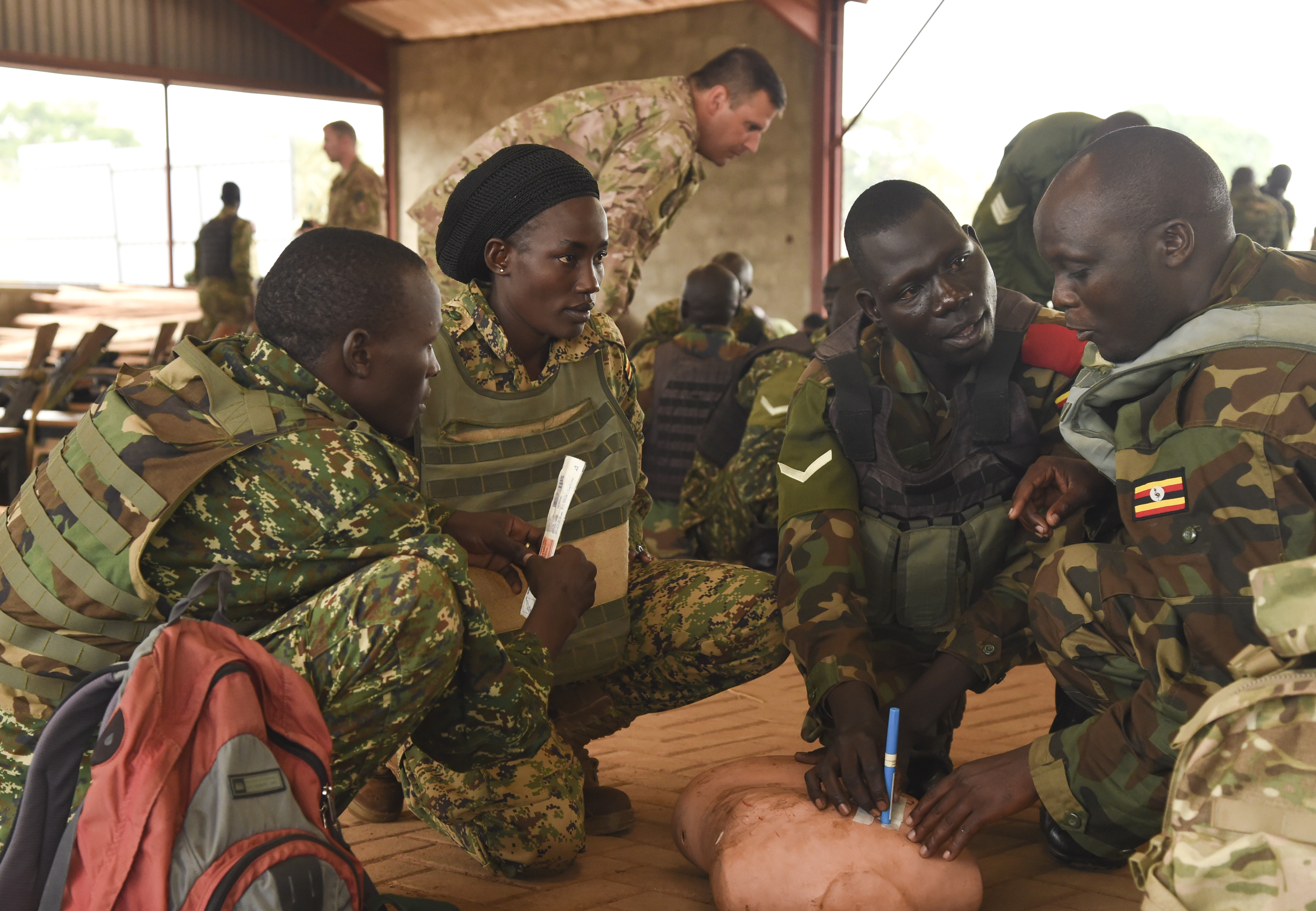 Uganda People's Defense Force (UPDF) soldiers with Ugandan Battle Group 22, insert a needle into the chest of a simulated chest wound casualty to prevent or treat tension pneumothorax while training at Camp Singo, Uganda, Feb. 28, 2017. The UPDF soldiers had three stations to attend during the Combat Lifesaver Course: response to chest trauma, needle-chest decompression, and opening and maintaining an airway. (U.S. Air National Guard photo by Staff Sgt. Penny Snoozy)