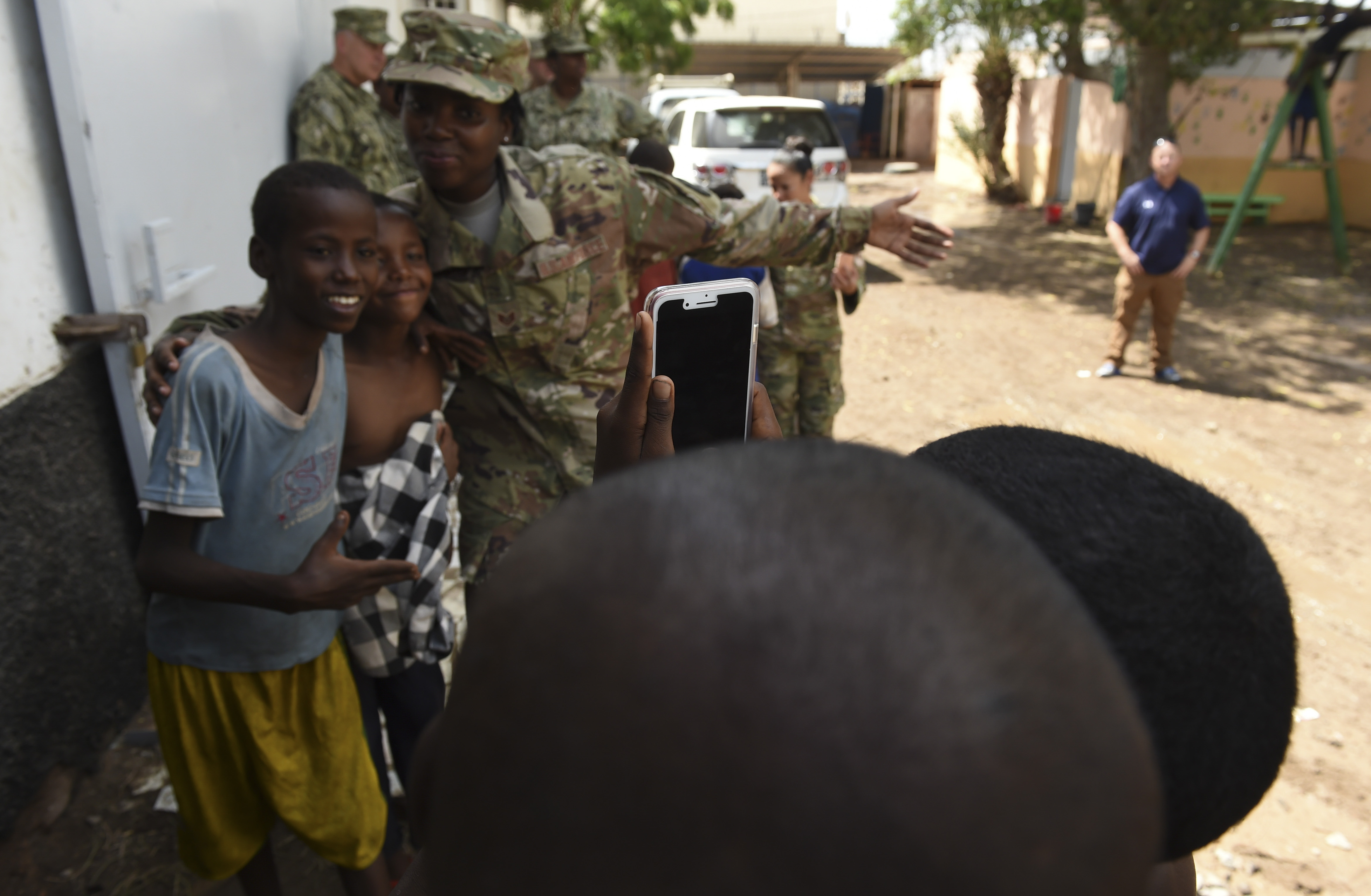 A child takes a photo of U.S. Air Force Staff Sgt. Grace Henderson posing with other children from Caritas Djibouti in downtown Djibouti, May 16, 2017. Henderson was one of more than 20 service members from Camp Lemonnier to visit Caritas Djibouti as part of an ongoing initiative to build partnerships with local religious leaders and humanitarian organizations. (U.S. Air Force photo by Eboni Prince)