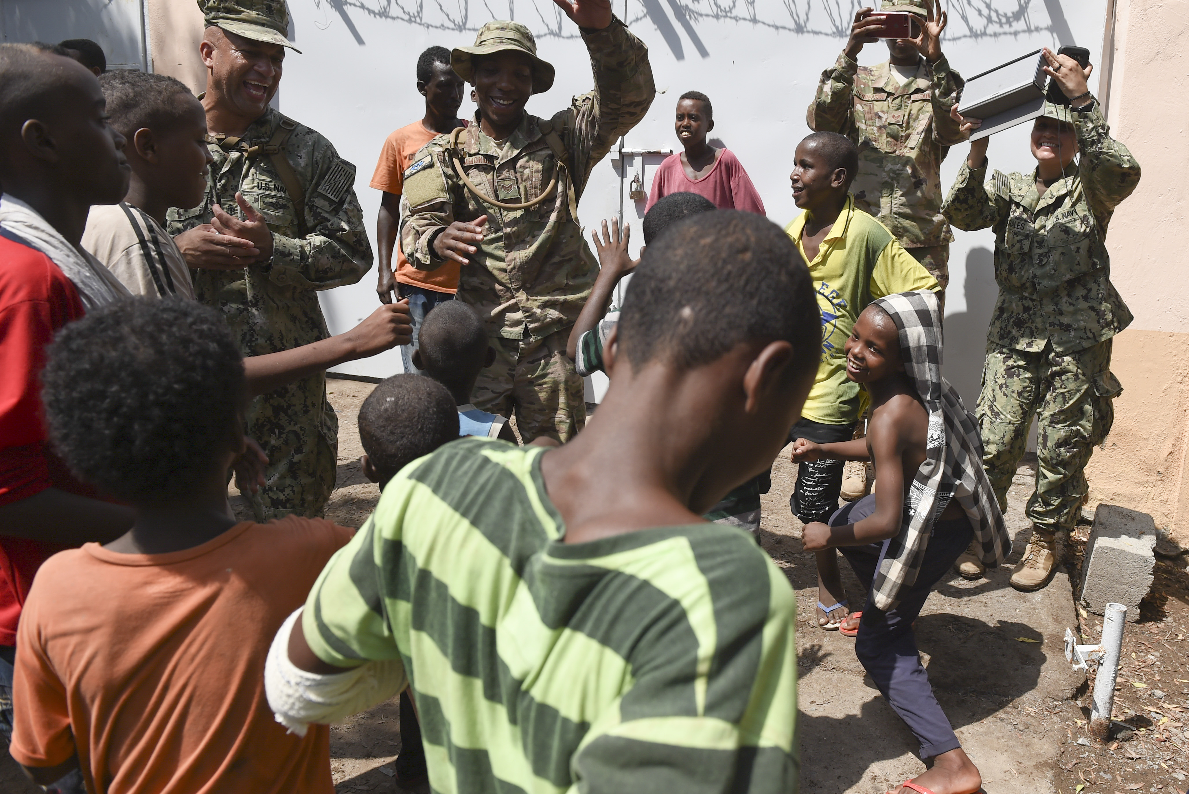 U.S. service members from Camp Lemonnier dance with children from Caritas Djibouti in downtown Djibouti, May 16, 2017. U.S. Service members assigned to the Combined joint Task Force - Horn of Africa, periodically visit with the mission to donate food items, toys, clothing and supplies. (U.S. Air Force photo by Eboni Prince)