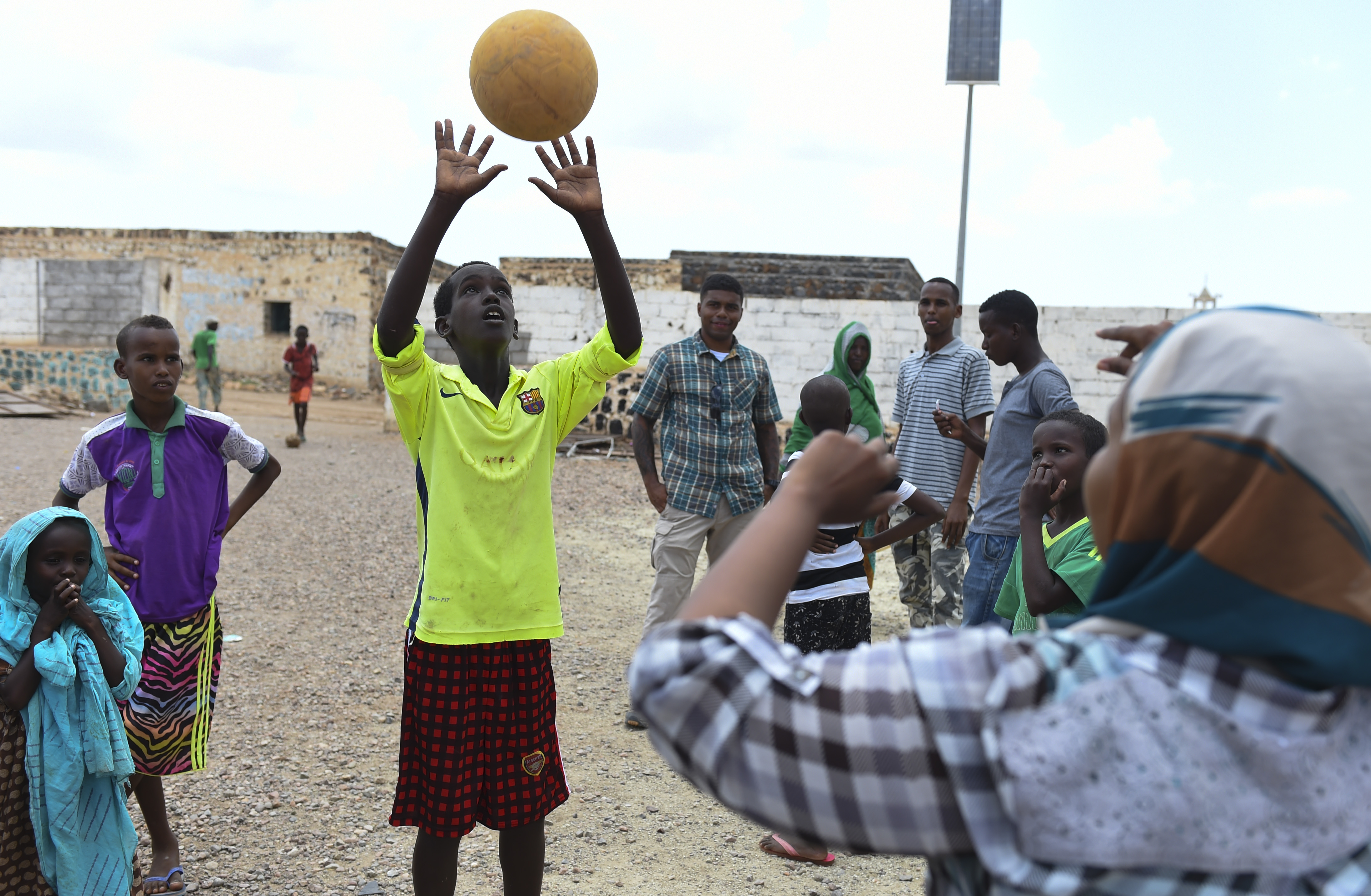 A child tosses a ball with Fatouma Omar Guedi, a language interpreter, in the village of Holhol, Djibouti, May 18, 2017. Language interpreters are essential to the success of civil affairs operations and act as liaisons between the military personnel and local key leaders in the Horn-of-Africa nations. (U.S. Air Force Photo by Eboni Prince)