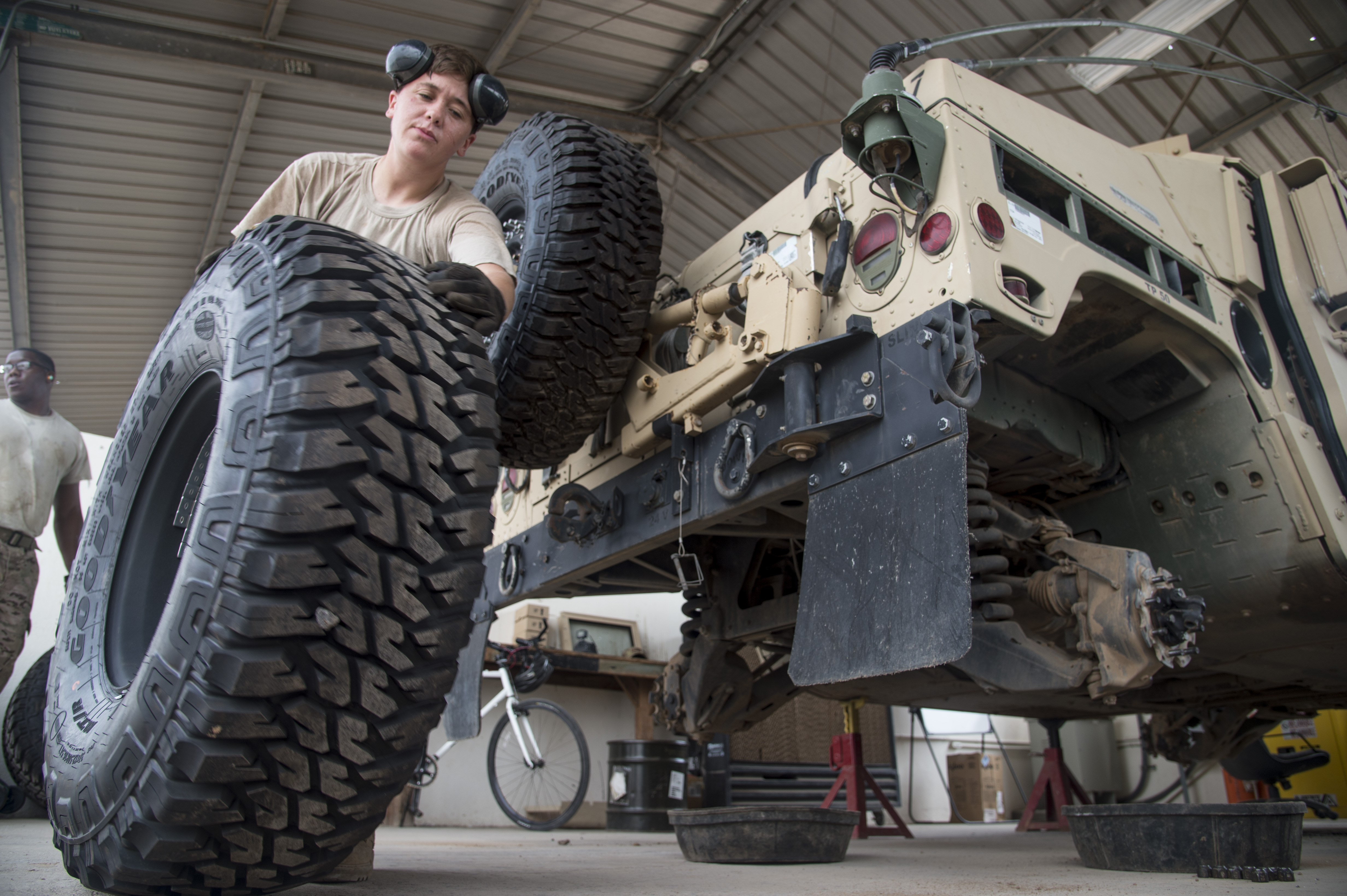 U.S. Army Spc. Kelsi May of the 1st Battalion, 153rd Infantry Regiment, deployed with the Combined Joint Task Force-Horn of Africa (CJTF-HOA) in Camp Lemonnier, Djibouti, rolls a tire to be replaced during a biannual service inspection of a Humvee, May 29, 2017. The soldiers maintain vehicles to support efforts in countering regional violent extremist organizations. (U.S. Air National Guard photo by Tech. Sgt. Joe Harwood)