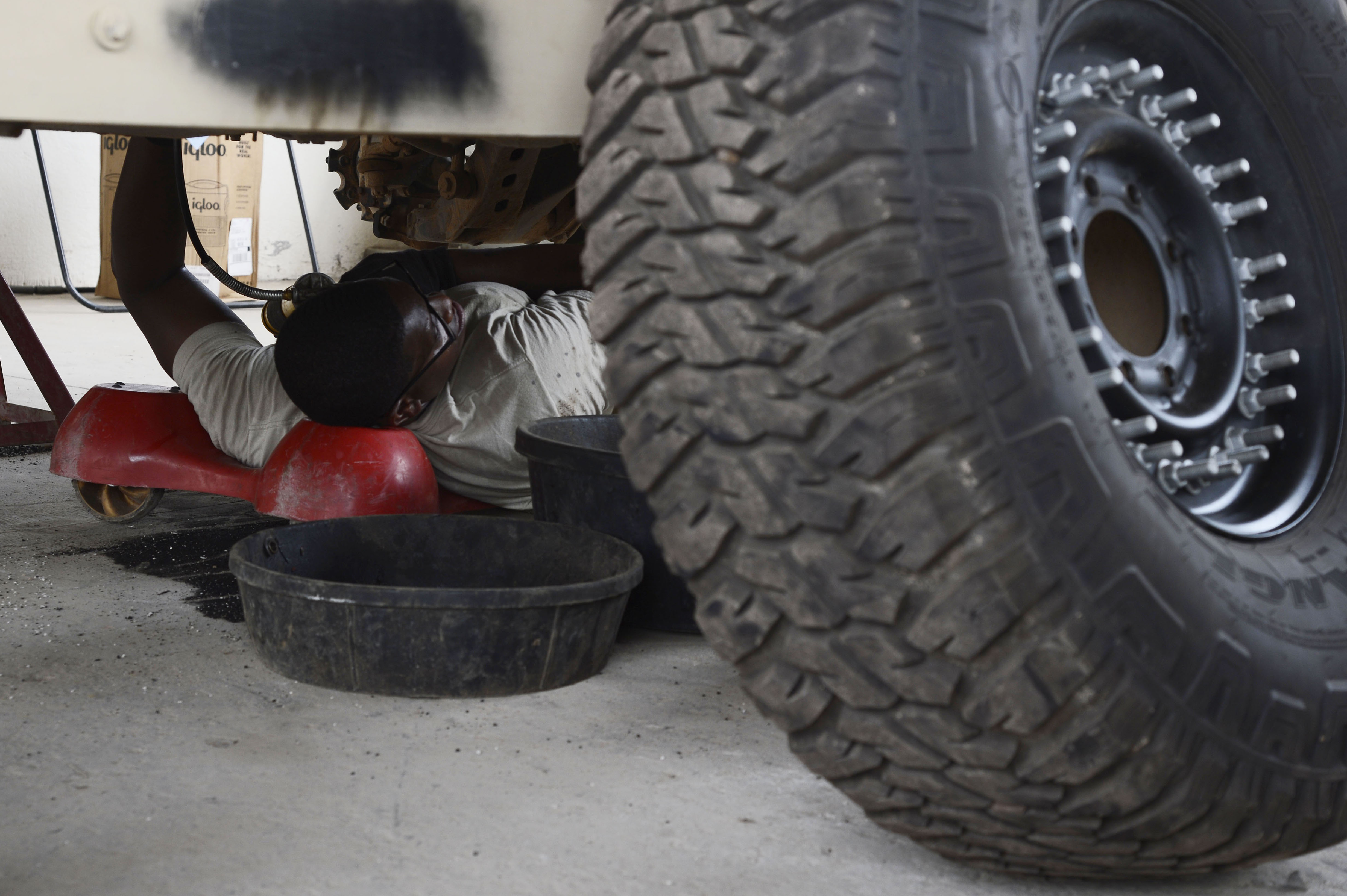U.S. Army Spc. Christopher Davis of the 1st Battalion, 153rd Infantry Regiment, deployed with Combined Joint Task Force-Horn of Africa (CJTF-HOA) at Camp Lemonnier, Djibouti, checks the undercarriage during a biannual service inspection of a Humvee, May 29, 2017. The soldiers maintain vehicles which support efforts in countering regional violent extremist organizations. (U.S. Air Force photo by Staff Sgt. Lindsay Cryer)