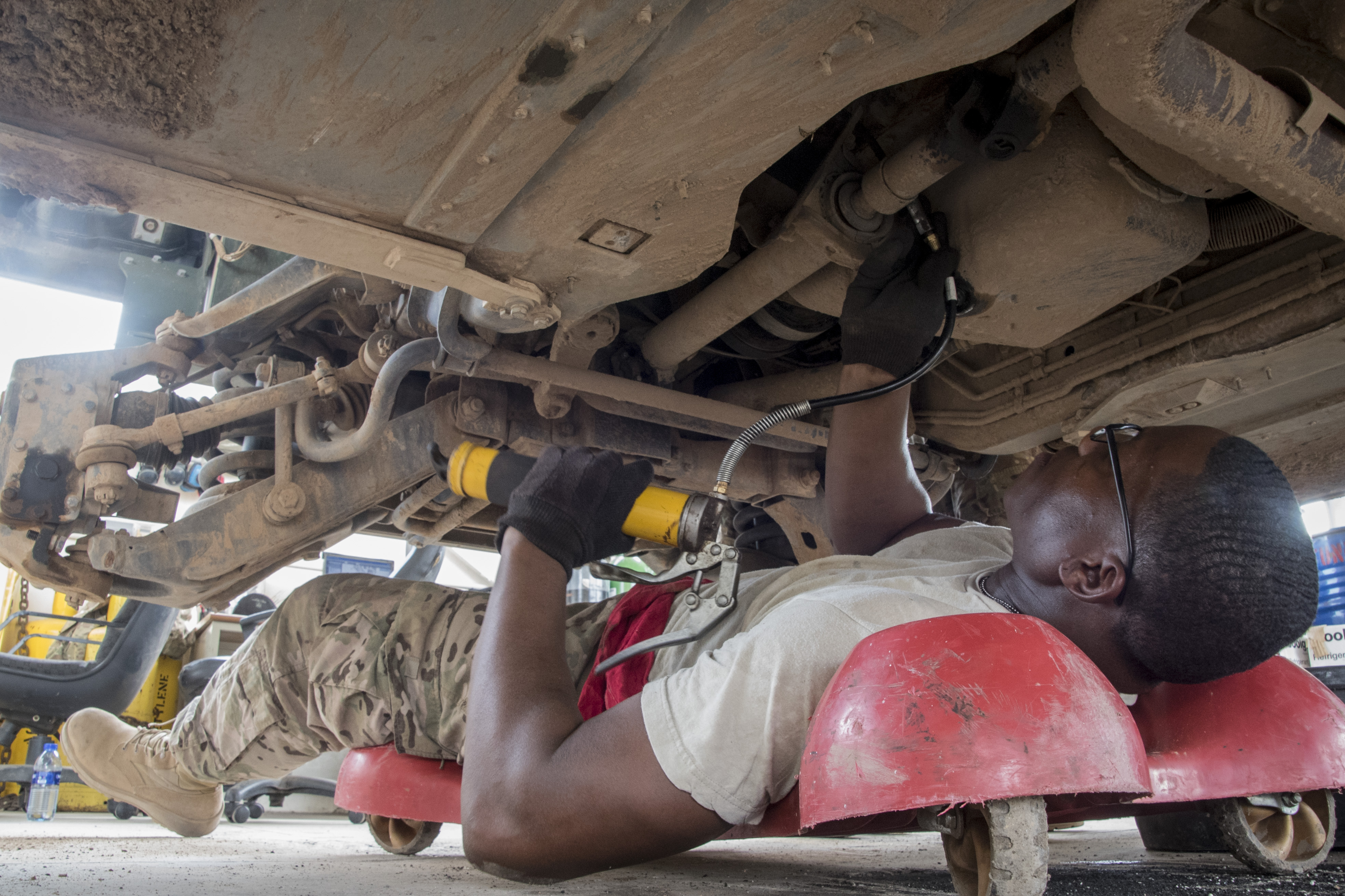 U.S. Army Spc. Christopher Davis of the 1st Battalion, 153rd Infantry Regiment, deployed with the Combined Joint Task Force-Horn of Africa (CJTF-HOA) in Camp Lemonnier, Djibouti, greases the undercarriage while performing a biannual service inspection on a Humvee, May 29, 2017. The Soldiers maintain vehicles to support efforts in countering regional violent extremist organizations. (U.S. Air National Guard photo by Tech. Sgt. Joe Harwood)