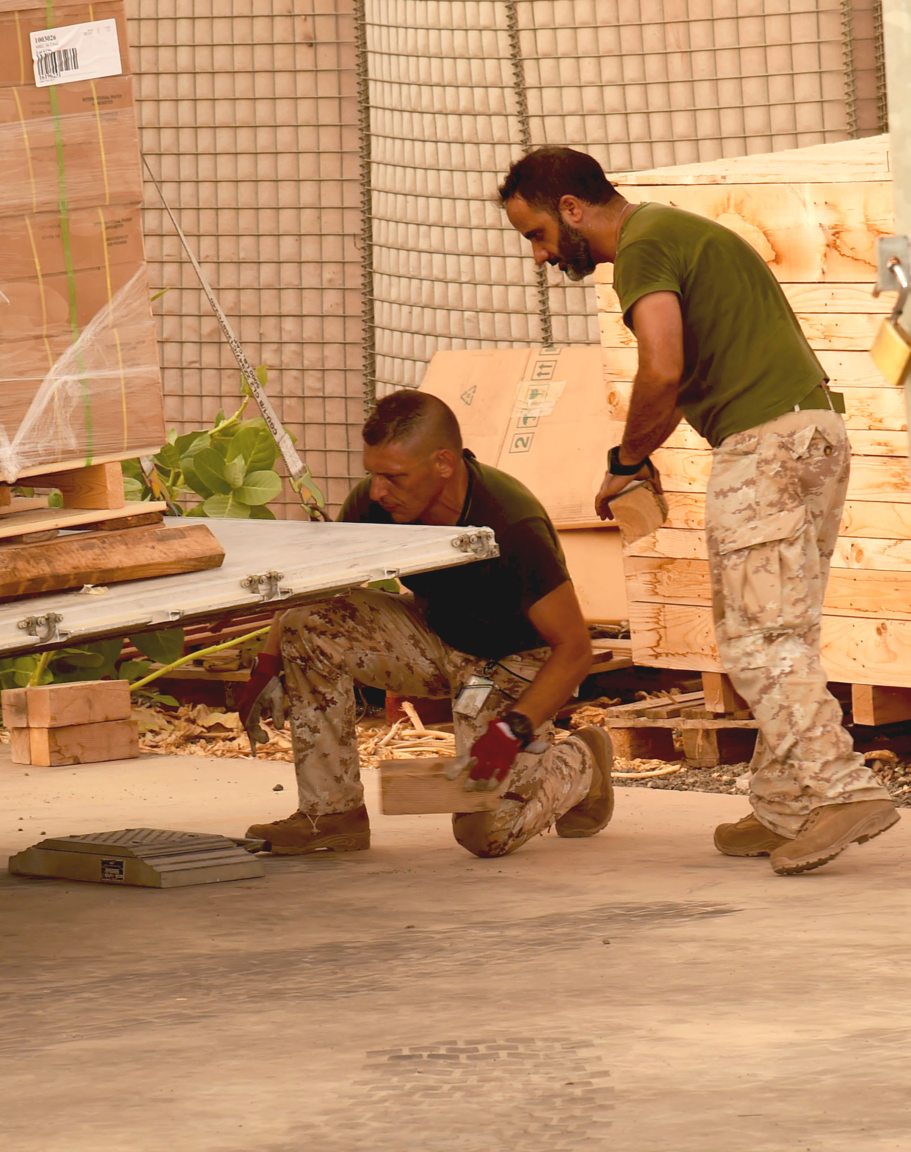 Two members of the Italian military retrieve a pallet of supplies from Combined Joint Task Force – Horn of Africa (CJTF-HOA) destined for Somalia via the Air Transportation and Refueling Exchange of Service (ATARES), at the Djibouti International Airport, Djibouti, June 6, 2017. The pallet was part of a proof-of-concept mission to see if CJTF-HOA would begin to implement the ATARES program. (U.S. Air National Guard photo by Tech. Sgt. Andria Allmond)