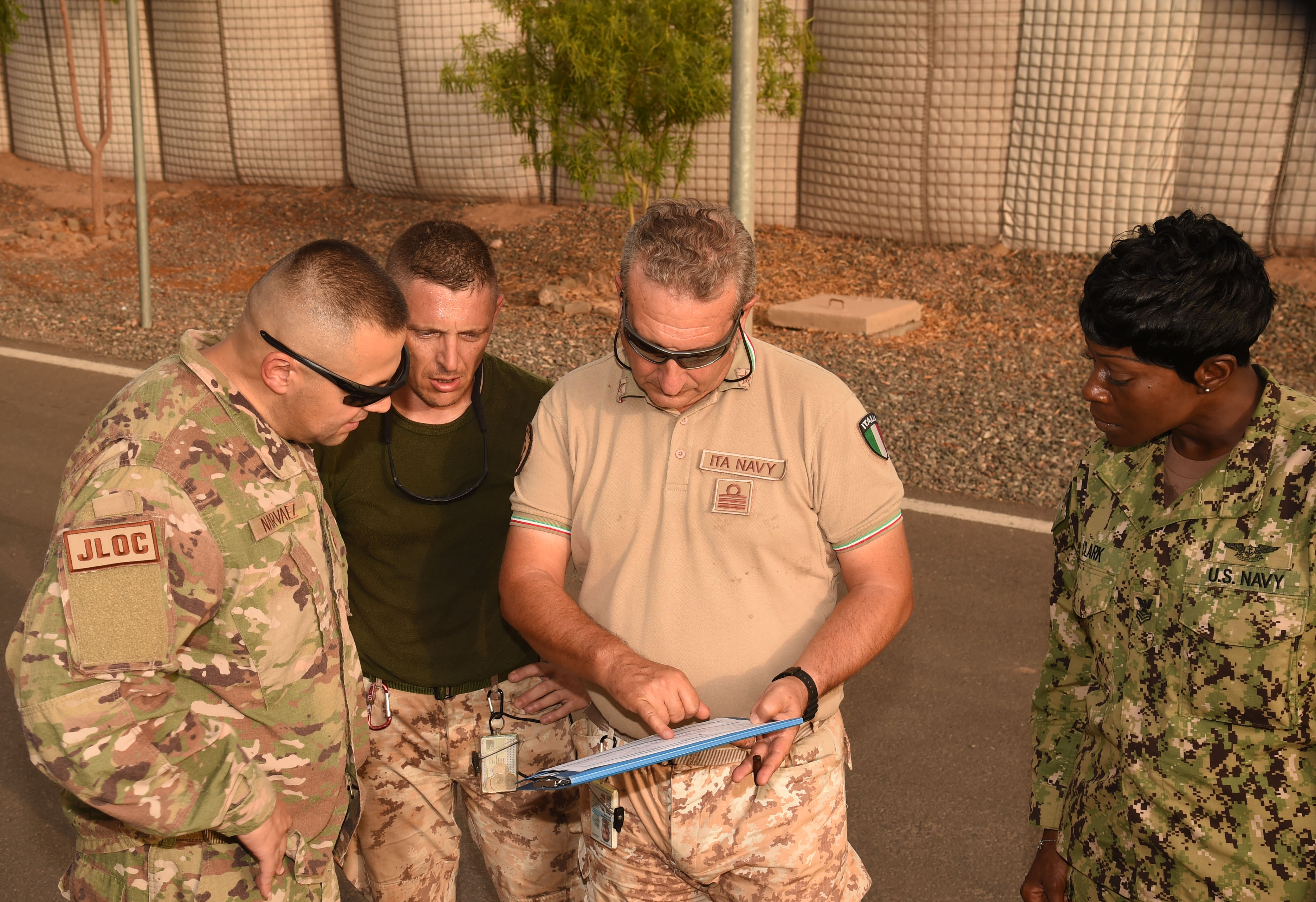 Left to right, U.S. Air Force Maj. Christopher Narvaez, Combined Joint Task Force – Horn of Africa (CJTF-HOA) Joint Logistics Operations Center deputy branch chief, ITA Air Force MCPO Roberto Scattolini and ITA Navy CDR Giovanni Cantamessa, and U.S. Navy Petty Officer 1st Class Chiquivia Clark review the paperwork for the U.S. military pallet destined for Somalia on an Italian military C-130 Hercules June 6, 2017, at the Djibouti International Airport, Djibouti. The two nations participated in CJTF-HOA's first Air Transportation and Refueling Exchange of Service. (U.S. Air National Guard Tech. Sgt. Andria Allmond)