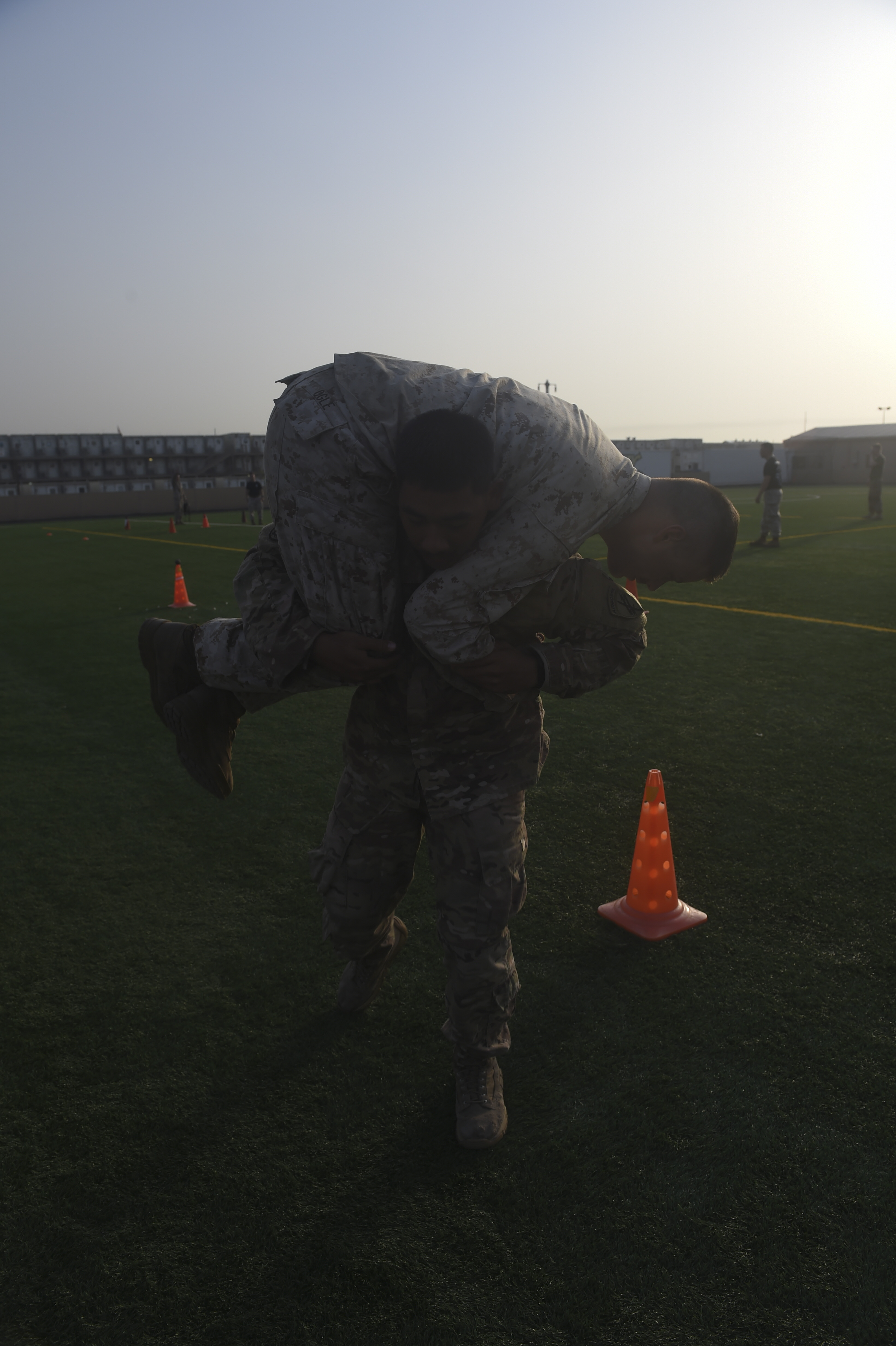 U.S. Army Spc. Kim-Sean Mam executes a fireman's carry with U.S. Marine Corps Cpl. Brandon Ogle, both assigned to Combined Joint Task Force-Horn of Africa, during the Corporal's Course at Camp Lemonnier, Djibouti, May 31, 2017. The course is a requirement for Marines in the enlisted grade of E-4, but here, all U.S. service members in the ranks of corporal, specialist, senior airman or petty officer third class were allowed to participate. (U.S. Air Force photo by Staff Sgt. Eboni Prince)