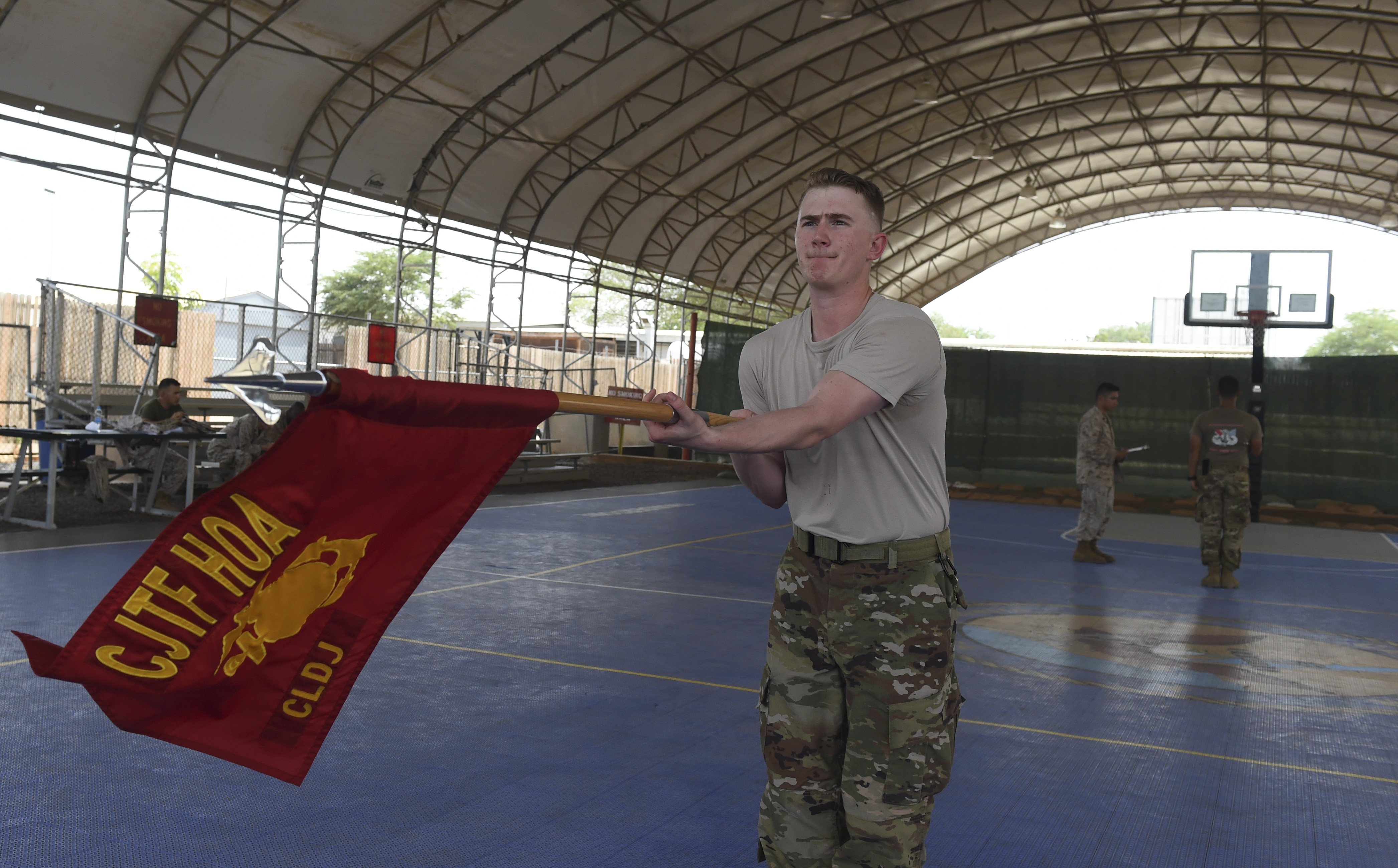 U.S. Air Force Senior Airman Christian Davis, assigned to Combined Joint Task Force-Horn of Africa, prepares to present arms with a guidon during the Corporal's Course at Camp Lemonnier, Djibouti, May 24, 2017. The course is a requirement for Marines in the enlisted grade of E-4, but here, all U.S. service members in the ranks of corporal, specialist, senior airman or petty officer third class were allowed to participate. (U.S. Air Force photo by Staff Sgt. Eboni Prince)
