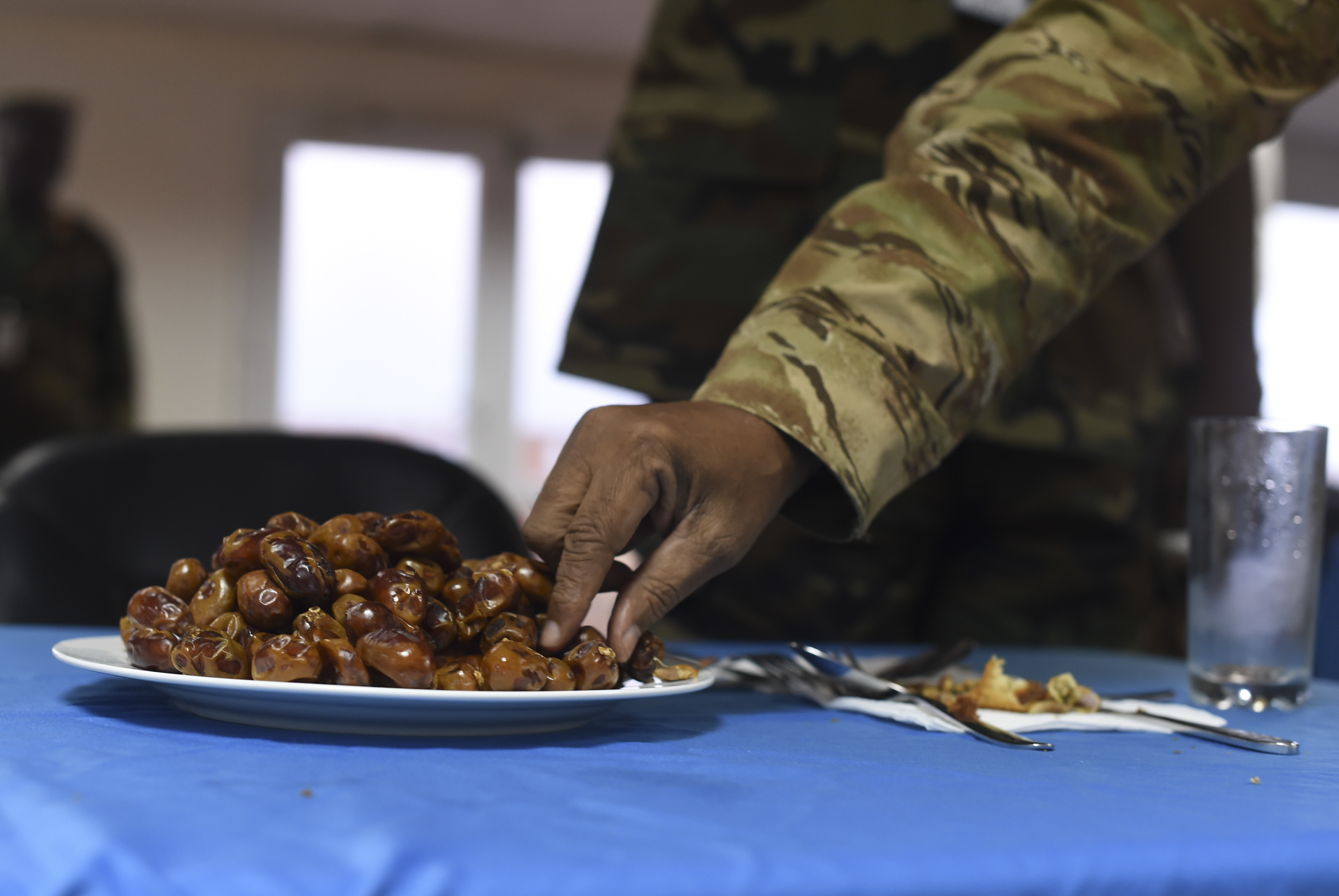 A member of the Somali National Army reaches for a date to break his fast during Ramadan at the Mogadishu International Airport, Mogadishu, Somalia, June 5, 2017. During Ramadan, Muslims abstain from food and drink, including water from dawn till dusk. After sunset, eating dates and drinking water traditionally breaks the fast. (U.S. Air Force Photo by Staff Sgt. Eboni Prince)