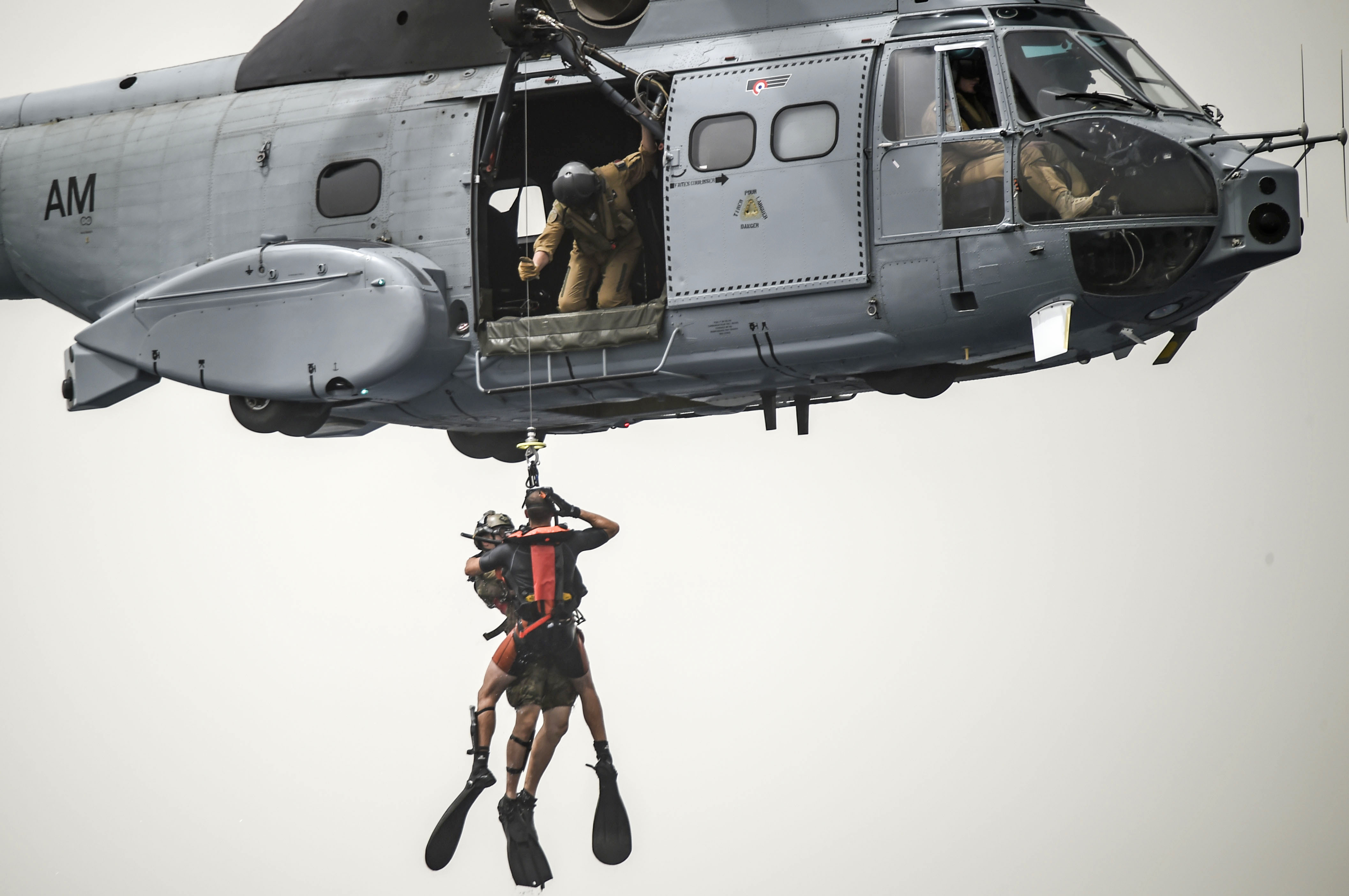 A French Air Force member assigned to the Transport Squadron ET 88 assists with hoisting another French Air Force member and a U.S. Air Force pararescueman from the 82nd Expeditionary Rescue Squadron, assigned to Combined Joint Task Force-Horn of Africa, into a French Air Force Aérospatiale SA 330 Puma helicopter during a bilateral water operations exercise in the Gulf of Tadjoura, July 3, 2017. This exercise marked the first bilateral rotary wing water operations exercise between the 82 ERQS and French forces. (U.S. Air Force photo by Staff Sgt. Eboni Prince)