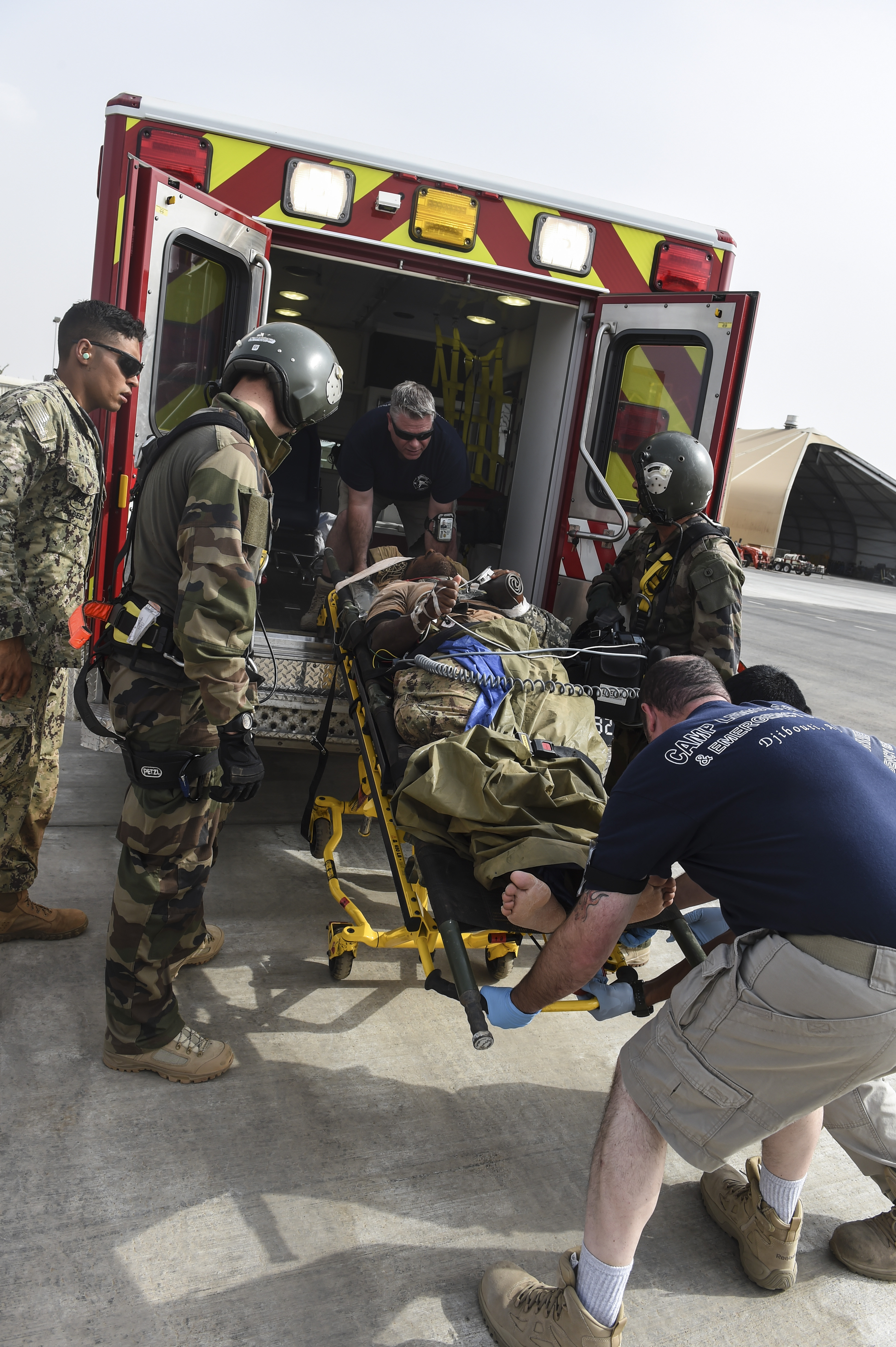 Emergency medical services personnel lift a patient on to an ambulance during a bilateral exercise with the Naval Mobile Construction Battalion One, a maneuver unit of the Combined Joint Task Force-Horn of Africa,  and French forces at Camp Lemonnier, July 20, 2017. CJTF-HOA conducts exercises to maintain readiness and evaluate capability of U.S. and international forces, or to establish/maintain relationships and contribute to capacity building. (U.S. Air Force photo by Staff Sgt. Eboni Prince)