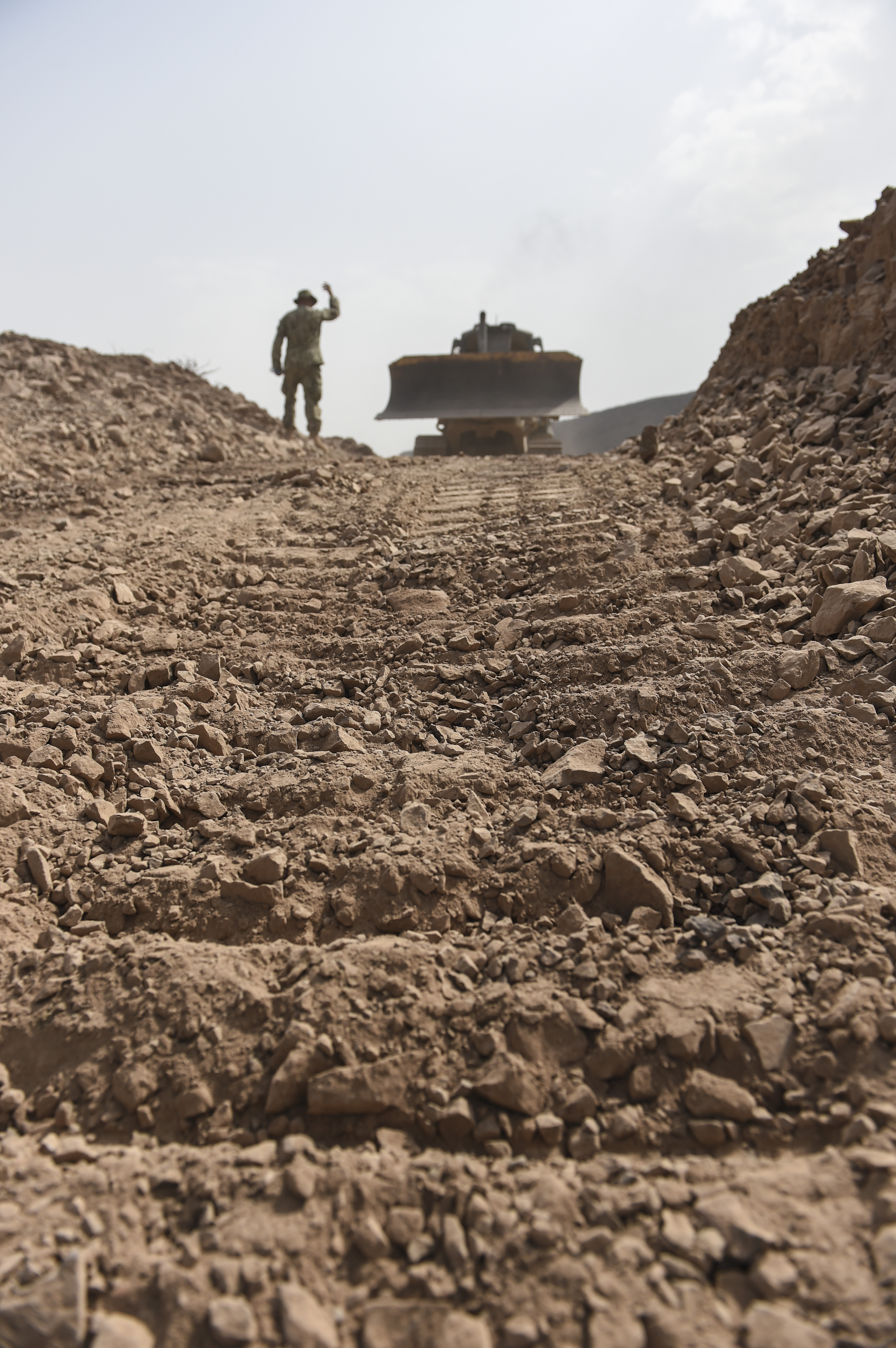 An equipment operator with the U.S. Naval Mobile Construction Battalion One directs another operator to proceed forward with a bulldozer at a range near Arta, Djibouti, July 27, 2017. NMCB One supports Combined Joint Task Force-Horn of Africa through the completion various construction projects throughout East Africa that aid promoting stability in the region. (U.S. Air Force photo by Staff Sgt. Eboni Prince)