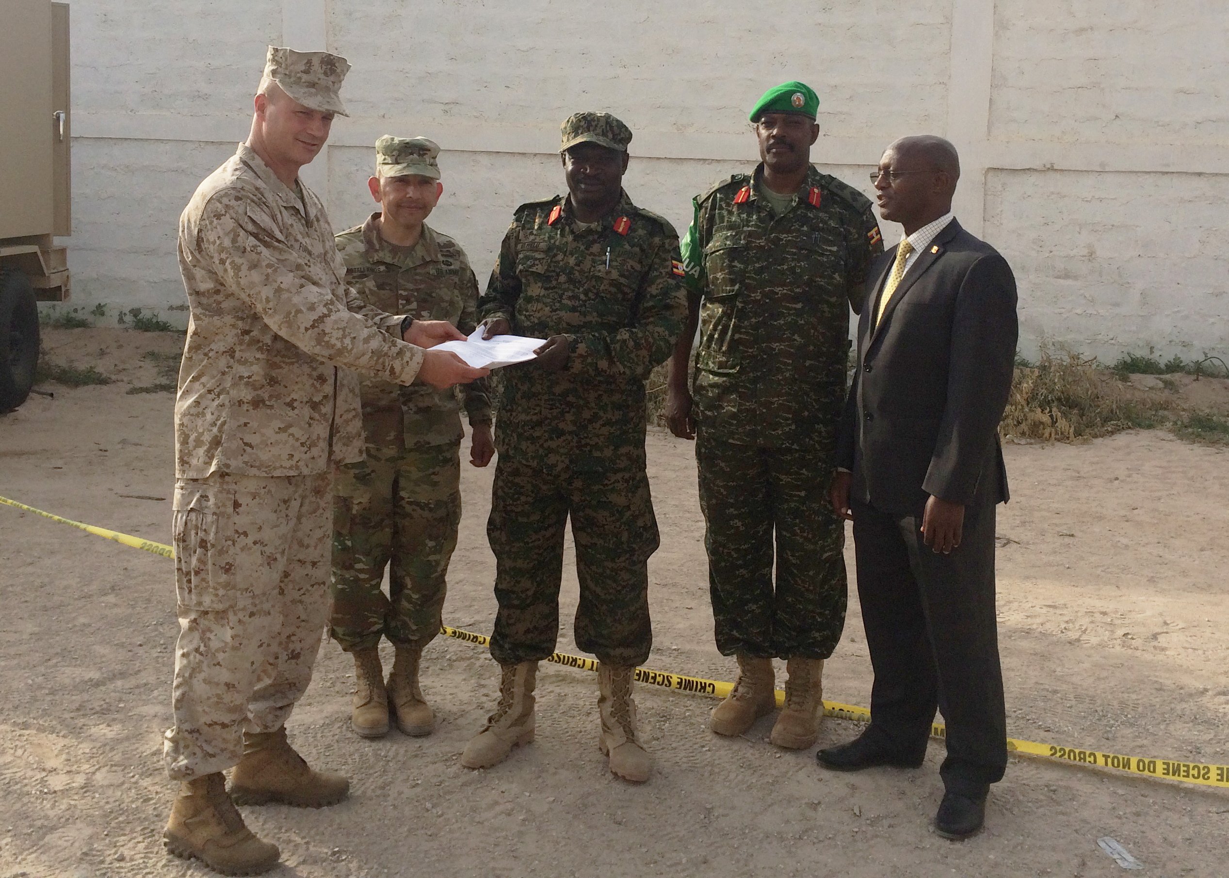 Combined Joint Task Force-Horn of Africa commander U.S. Marine Brig. Gen. David Furness and U.S. Army Brig. Gen. Miguel Castellanos, deputy commanding general for CJTF-HOA in Somalia and Mogadishu Coordination Cell director, hand over documentation of U.S. military force protection assets that are being provided to Uganda People's Defense Force (UPDF) July 25, at the Mogadishu Coordination Cell, Somalia.