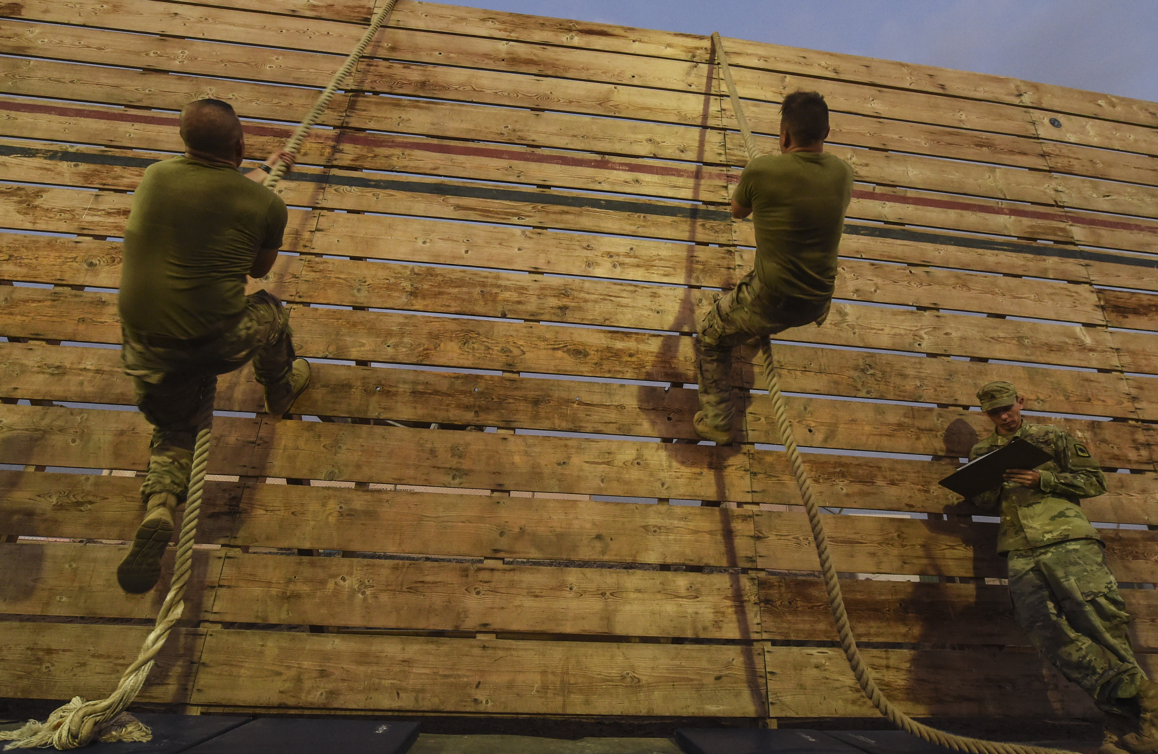 U.S. military members complete a wall rope climb during a physical training test at Camp Lemonnier, Djibouti, Aug. 5, 2017. The test was in preparation for an upcoming multi-day French Desert Commando Course that will challenge participants physically and mentally through land and water obstacles, combat scenarios and extreme endurance exercises while surviving in austere field conditions. (U.S. Air Force photo by Staff Sgt. Eboni Prince)