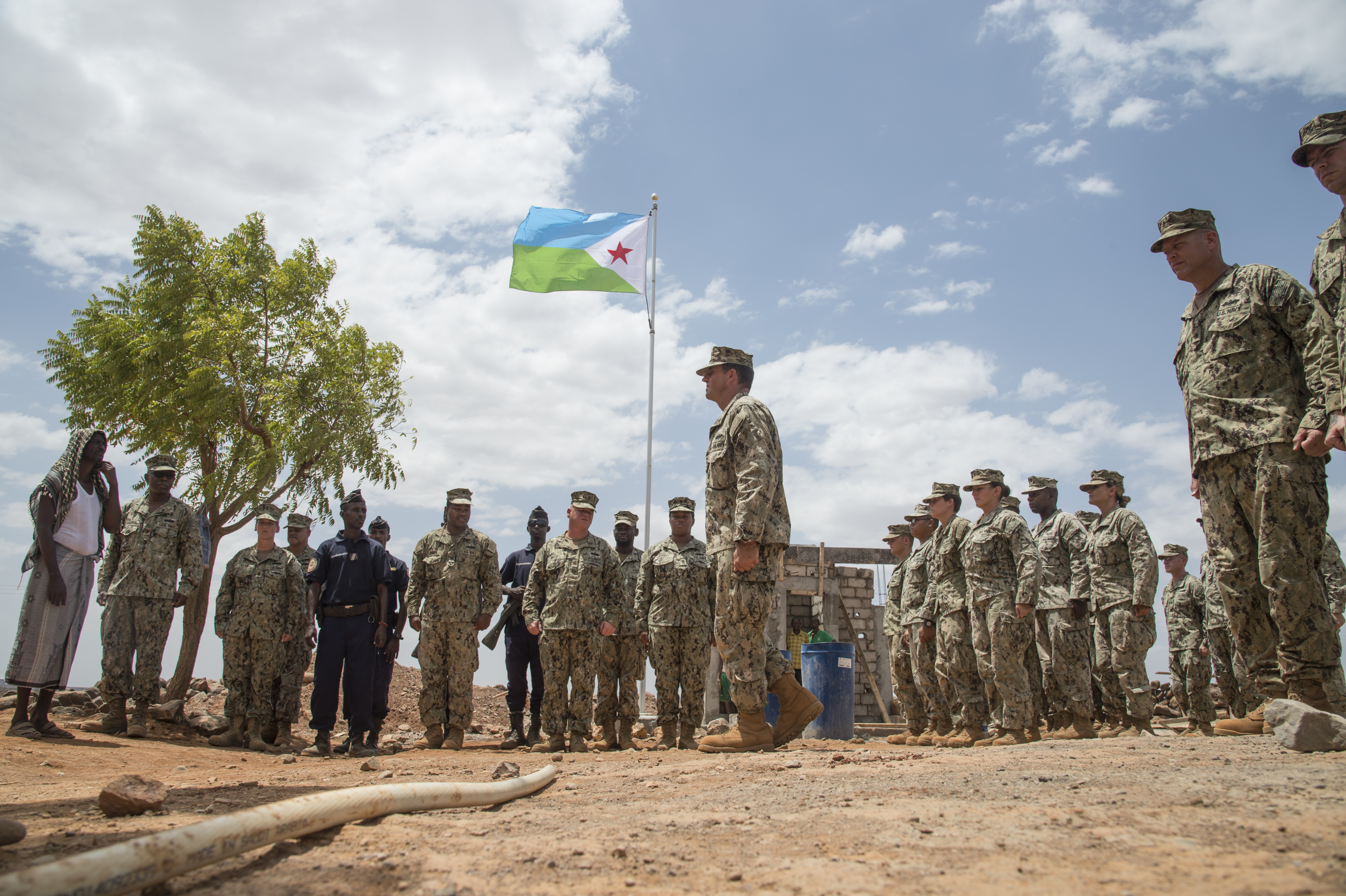 Naval Mobile Construction Battalion ONE officer-in-charge U.S. Navy Lt. Cmdr. Jason Ward introduces village Chief Hassan Diama to Seabees assigned to Combined Joint Task Force-Horn of Africa gathered at a construction site in a remote village in the Arta region of Djibouti during a flag dedication ceremony, Aug. 17, 2017. The project was started by NMCB 1, now replaced by NMCB 133, who will continue working on the project. (U.S. Air National Guard photo by Tech. Sgt. Joseph Harwood)
