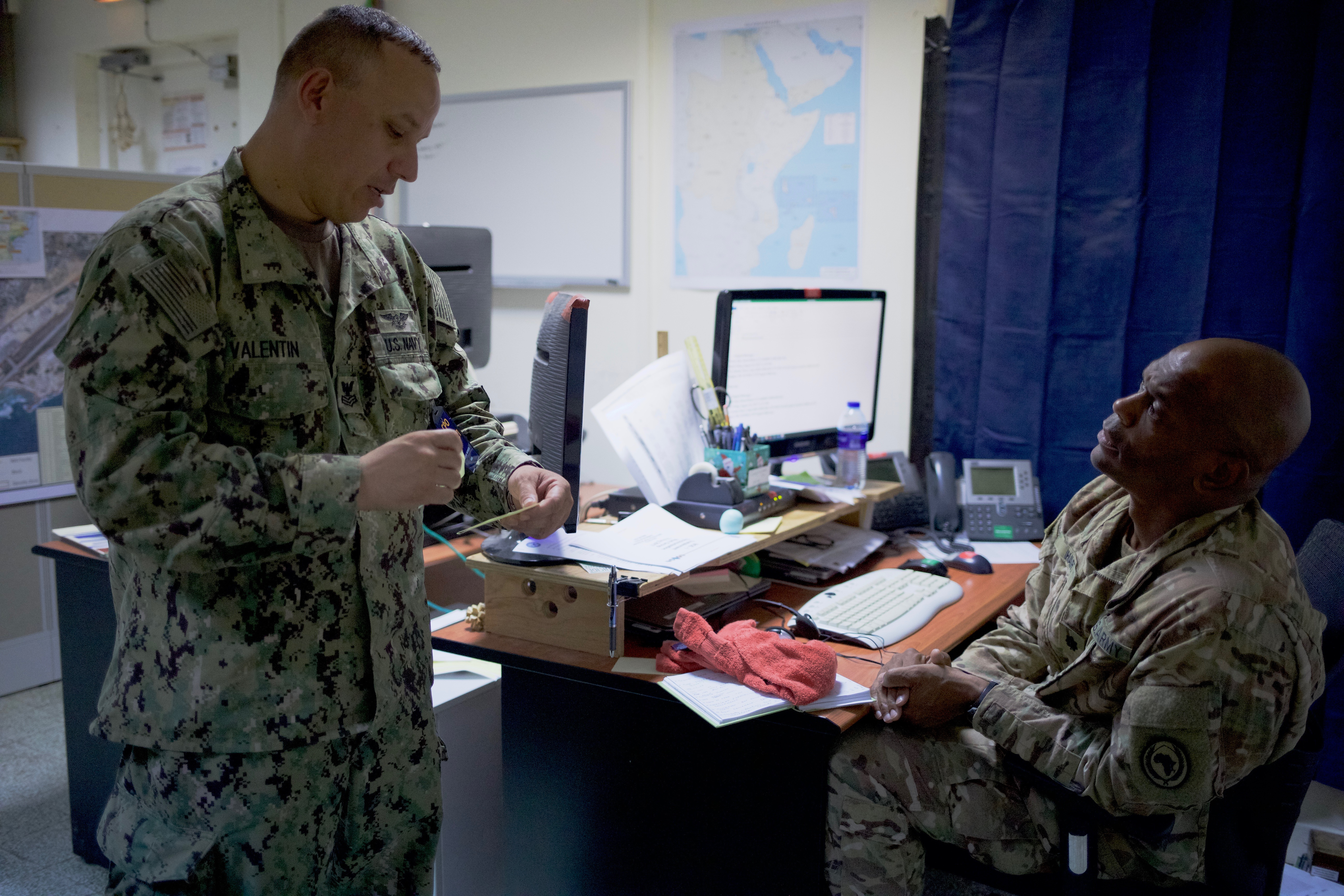 U.S. Navy Petty Officer 1st Class Francisco Valentin, fuels management specialist with the Combined Joint Task Force-Horn of Africa Logistics Directorate's Base Operating Support-Integrator office, provides updates on support resources to Lt. Col. Derek Hart, director of BOS-I, at Camp Lemonnier, Djibouti, August 18, 2017.  Hart is responsible for overseeing the continuous flow and coordination of mission-essential resources to forward-deployed U.S. service members throughout Somalia. U.S. Africa Command designated CJTF-HOA as BOS-I in August 2016, putting the 500-person task force in charge of coordinating the efficient use of mission resources to sustain U.S. forces in forward operating locations in Somalia. (U.S. Army photo by Capt. Alán Ortiz)