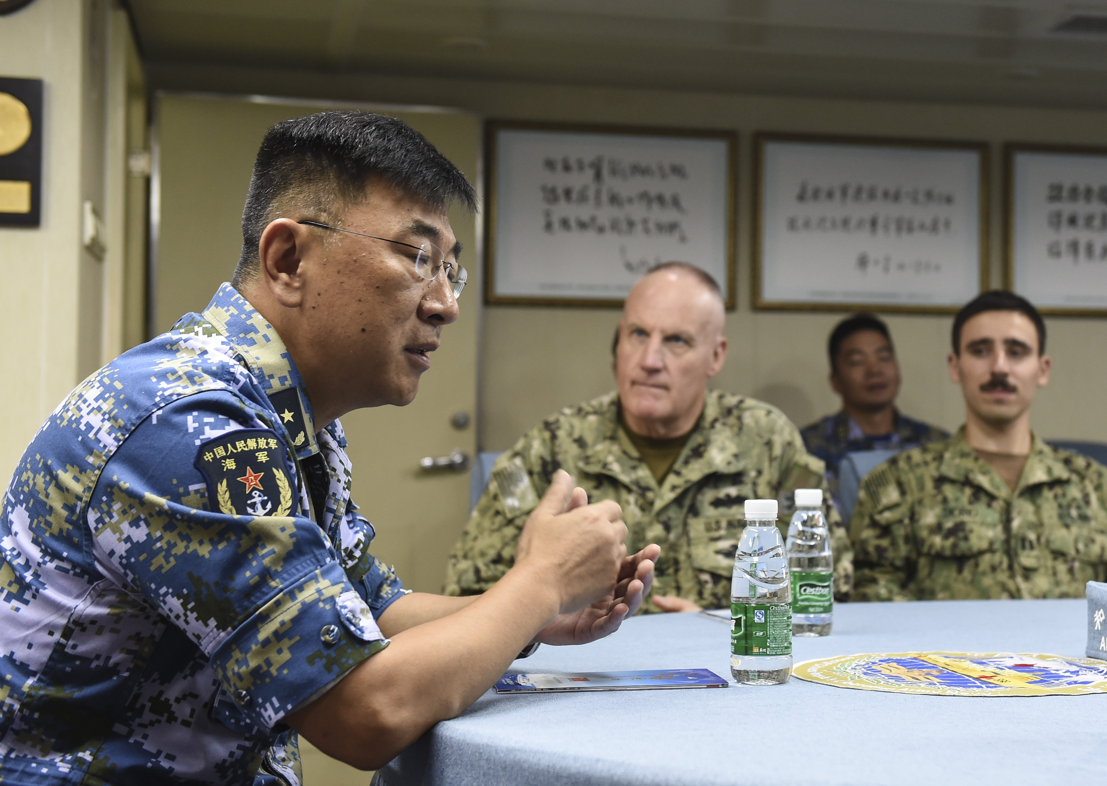 Chinese Navy Rear Admiral Guan Bolin speaks with Expeditionary Medical Facility personnel assigned to Camp Lemonnier during a tour of the ship's capabilities, August 28, 2017. Bolin expressed his gratitude for their visit and offered use of the ship, if needed, for emergency medical services. (U.S. Air Force photo by Staff Sgt. Eboni Prince)