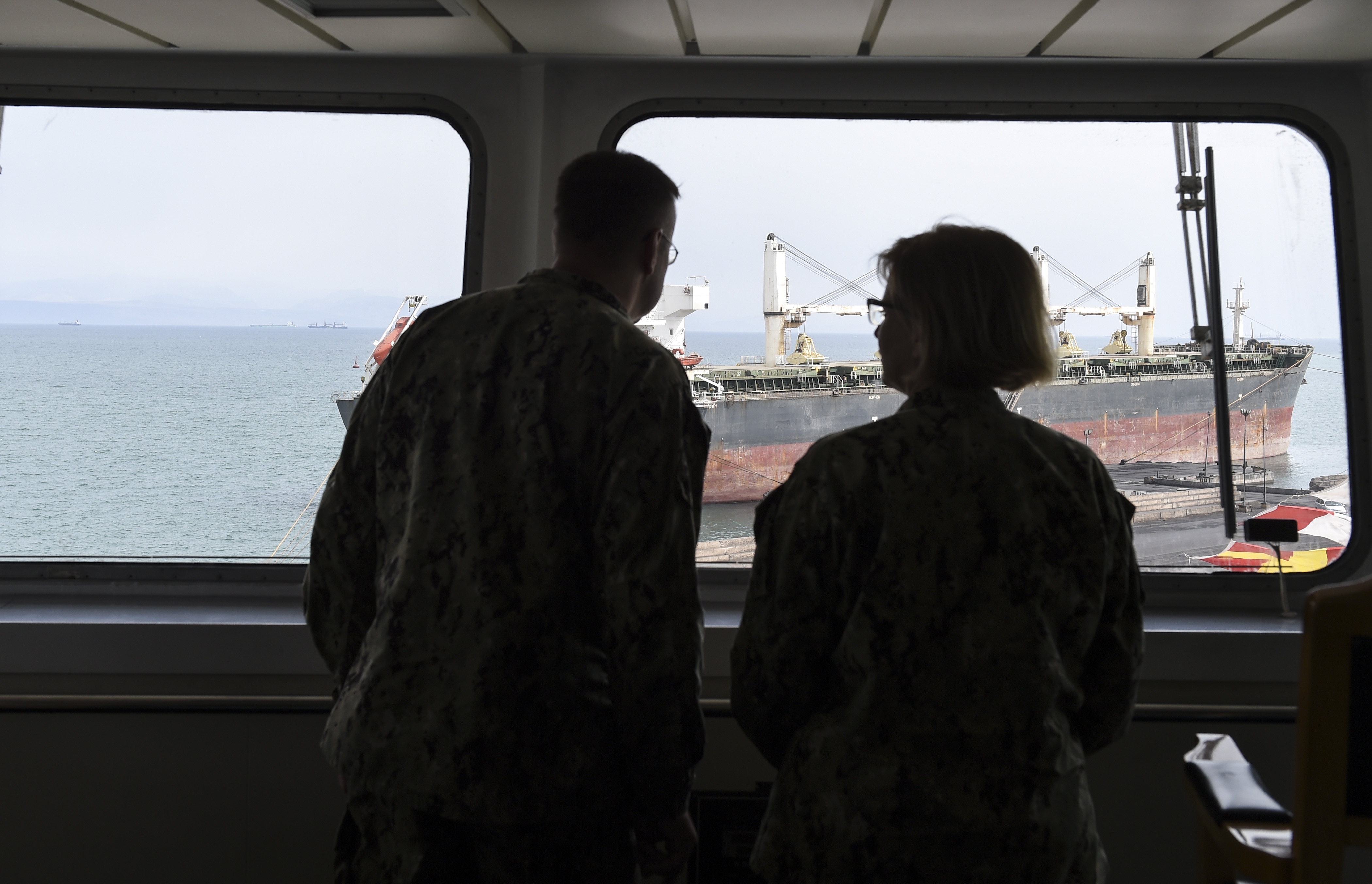 U.S. Navy Sailors assigned to the Expeditionary Medical Facility at Camp Lemonnier look out a window at ships in the Port of Djibouti, August 28, 2017. Medical personnel from Camp Lemonnier visited the Ark Peace and received a tour from Chinese medical personnel to highlight the ship's capabilities. (U.S. Air Force photo by Staff Sgt. Eboni Prince)