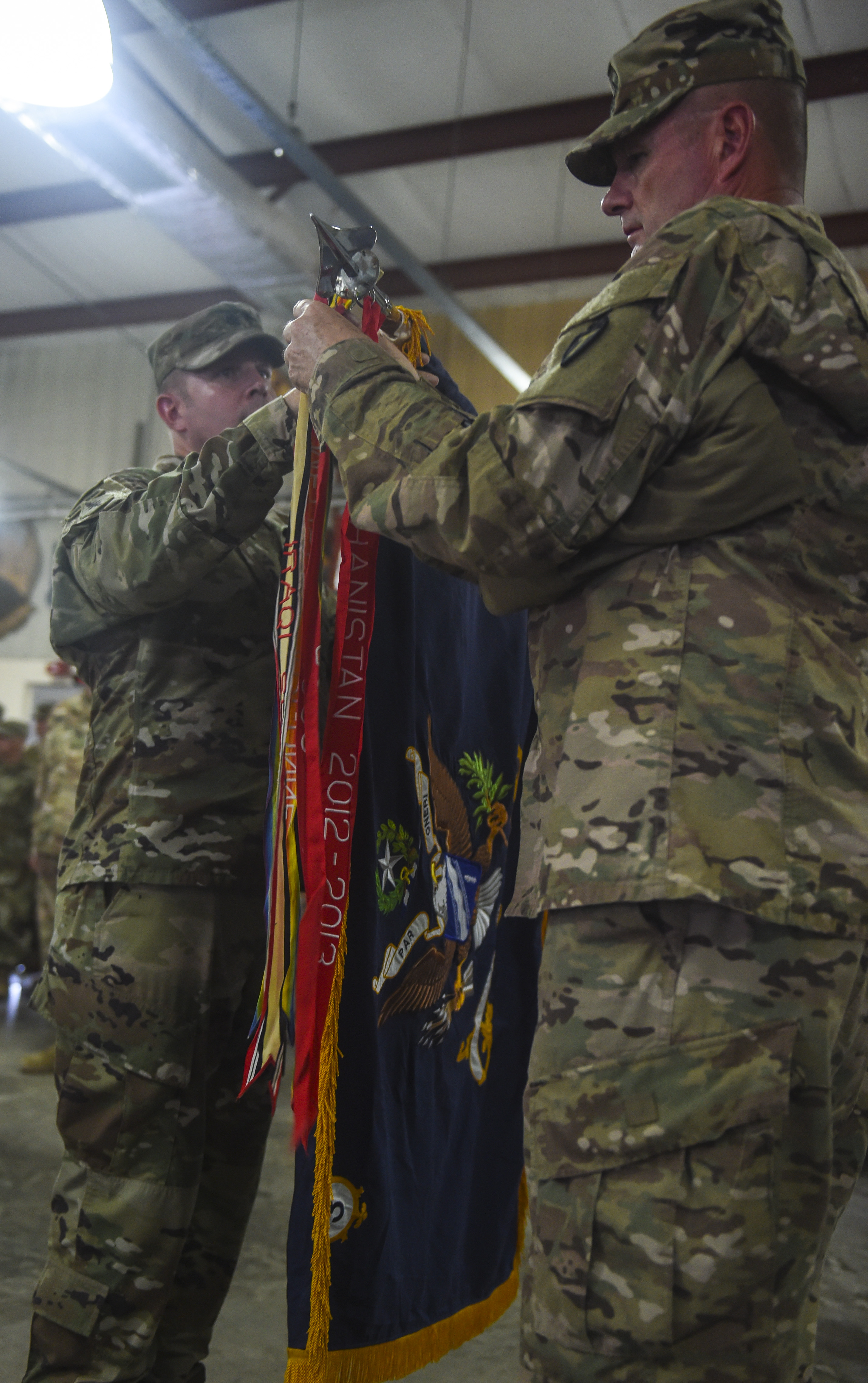 Third Battalion, 144th Infantry Regiment leaders U.S. Army Lt. Col. Ross Walker (left), battalion commander, and U.S. Army Command Sgt. Maj. Clinton Petty, command sergeant major, unfurl the unit's colors during a transfer of authority ceremony at Camp Lemonnier, Djibouti, Nov. 1, 2017. The transfer of authority ceremony is a longstanding Army tradition that signifies when a new unit takes over full responsibility for a mission. The 3-144th IN took responsibility from the 1st Battalion, 153rd Infantry Regiment. (U.S. Air Force photo by Staff Sgt. Timothy Moore)