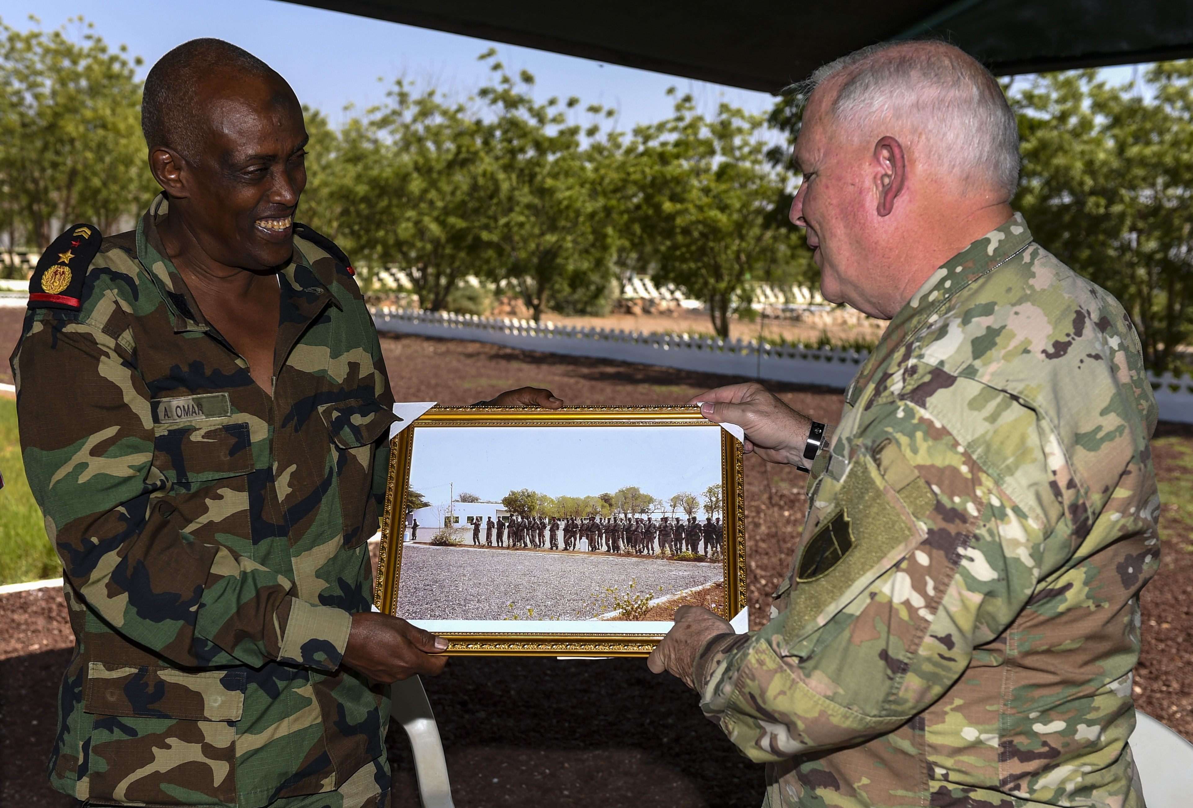 Djibouti Armed Forces (FAD) Lt. Col. A. Omar (left) presents a gift to U.S. Army National Guard Brig. Gen. Benjamin Adams III, Kentucky National Guard deputy adjutant general, during a State Partnership Program visit to the FAD military training center at Holhol, Djibouti, Nov. 14, 2017. The SPP is a joint U.S. Department of Defense program that matches a state's National Guard with a1 nation to promote enduring, mutually beneficial security relationships. (U.S. Air Force photo by Staff Sgt. Timothy Moore)