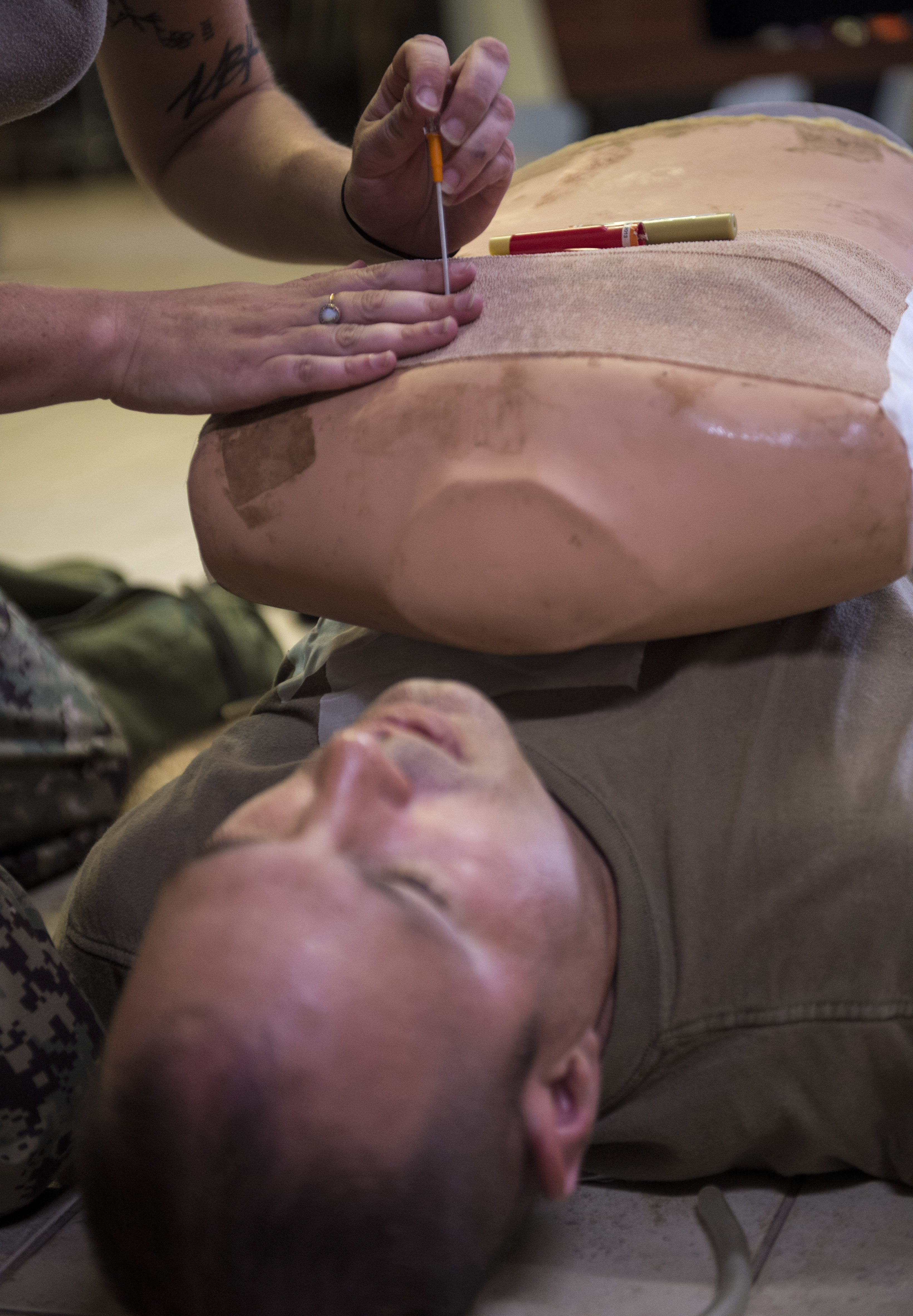 U.S. Navy Utilitiesman 3rd Class Amanda Stone, assigned to Naval Mobile Construction Battalion 133, attached to the Combined Joint Task Force – Horn of Africa, performs a needle chest decompression (NCD) on a simulated casualty during the final assessment of a U.S. Army Combat Lifesaver Course held at Camp Lemonnier, Djibouti, Dec. 1, 2017. An NCD is used when air enters the chest cavity but can't escape, creating pressure on a lung. The five-day course focused on teaching students how to administer lifesaving tactical medical care to wounded service members on the battlefield. (U.S. Air Force photo by Staff Sgt. Timothy Moore)