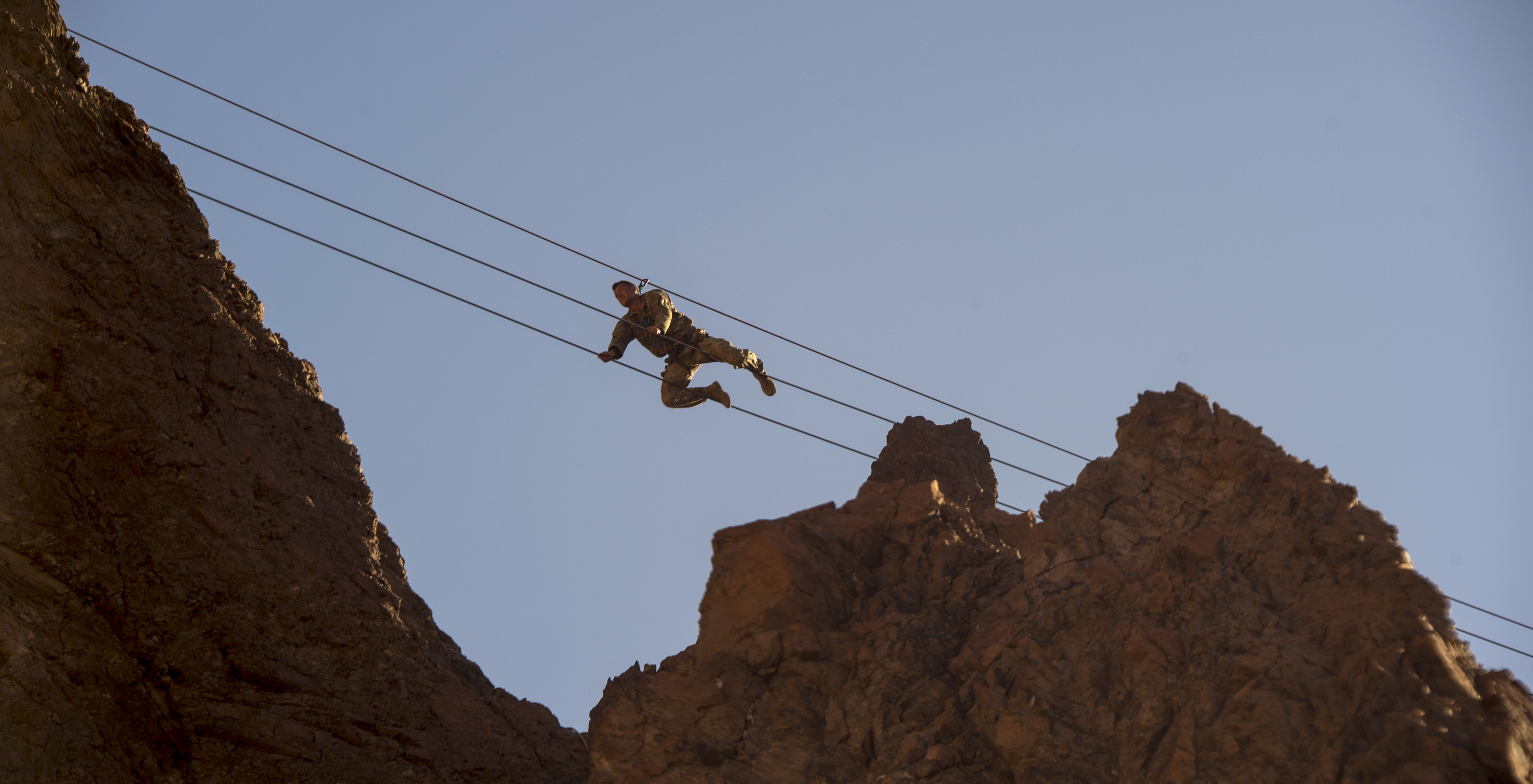 A. U.S. Army Soldier assigned to the Combined Joint Task Force - Horn of Africa, crawls across suspended wires during the mountain obstacle portion of the French Desert Commando Course held at Arta, Djibouti, Dec. 3, 2017. Thirty U.S. service members participated in the obstacle course alongside French marines assigned to the 5th Overseas Interarms Regiment, Djibouti. (U.S. Air Force photo by Staff Sgt. Timothy Moore)