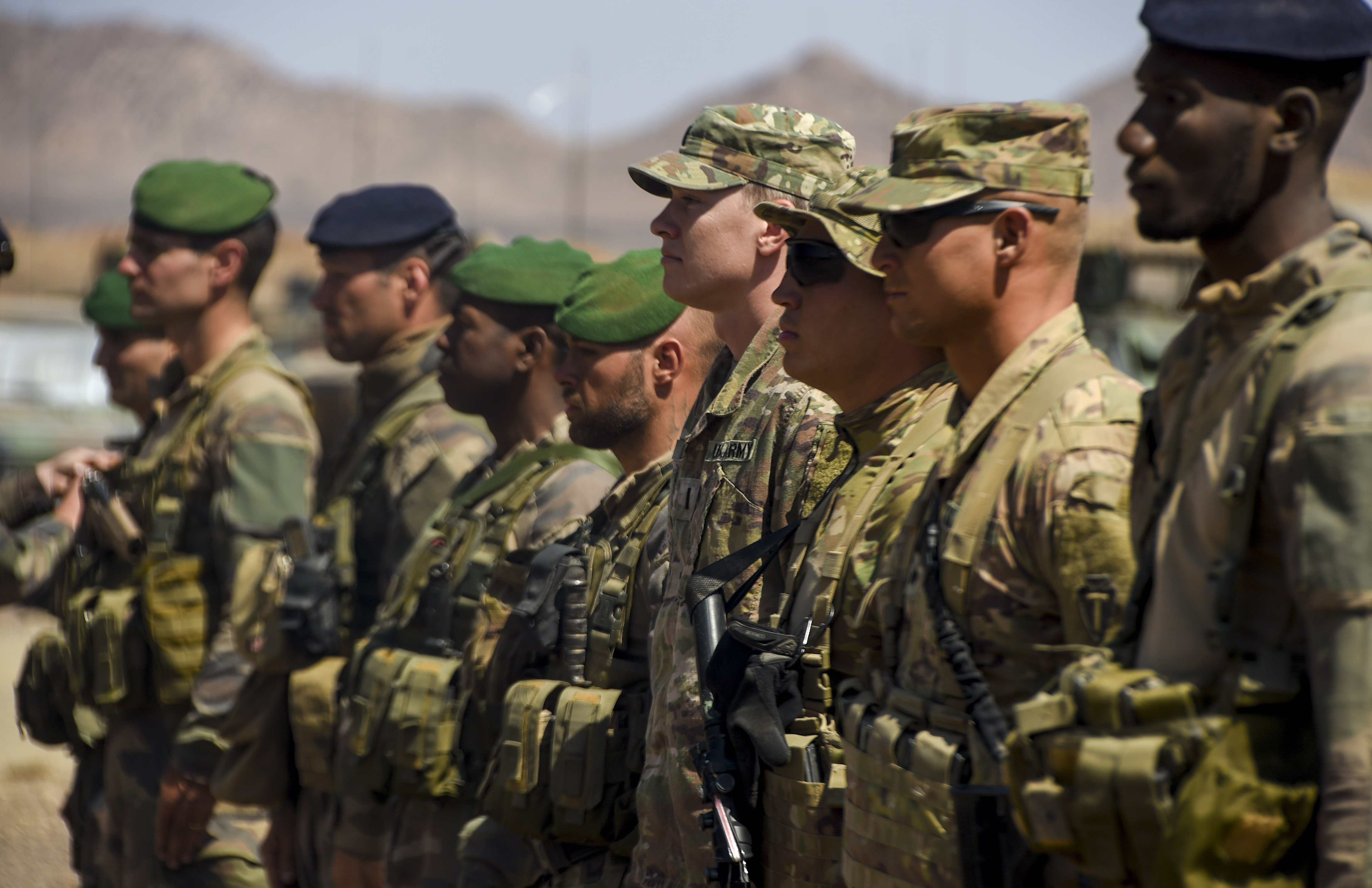 U.S. Army 1st Lt. Nicholas Bergam, Spc. Richard Baker, and Sgt. Kyle Parrin, all assigned to Combined Joint Task Force - Horn of Africa (CJTF-HOA), and French marines assigned to the 5th Overseas Interarms Regiment stand in line to receive their French Desert Commando Course pins during the graduation ceremony near Ali Sabieh, Djibouti, Dec. 7, 2017. The Soldiers and marines received special recognition as honor graduates of the course. (U.S. Air Force photo by Staff Sgt. Timothy Moore)