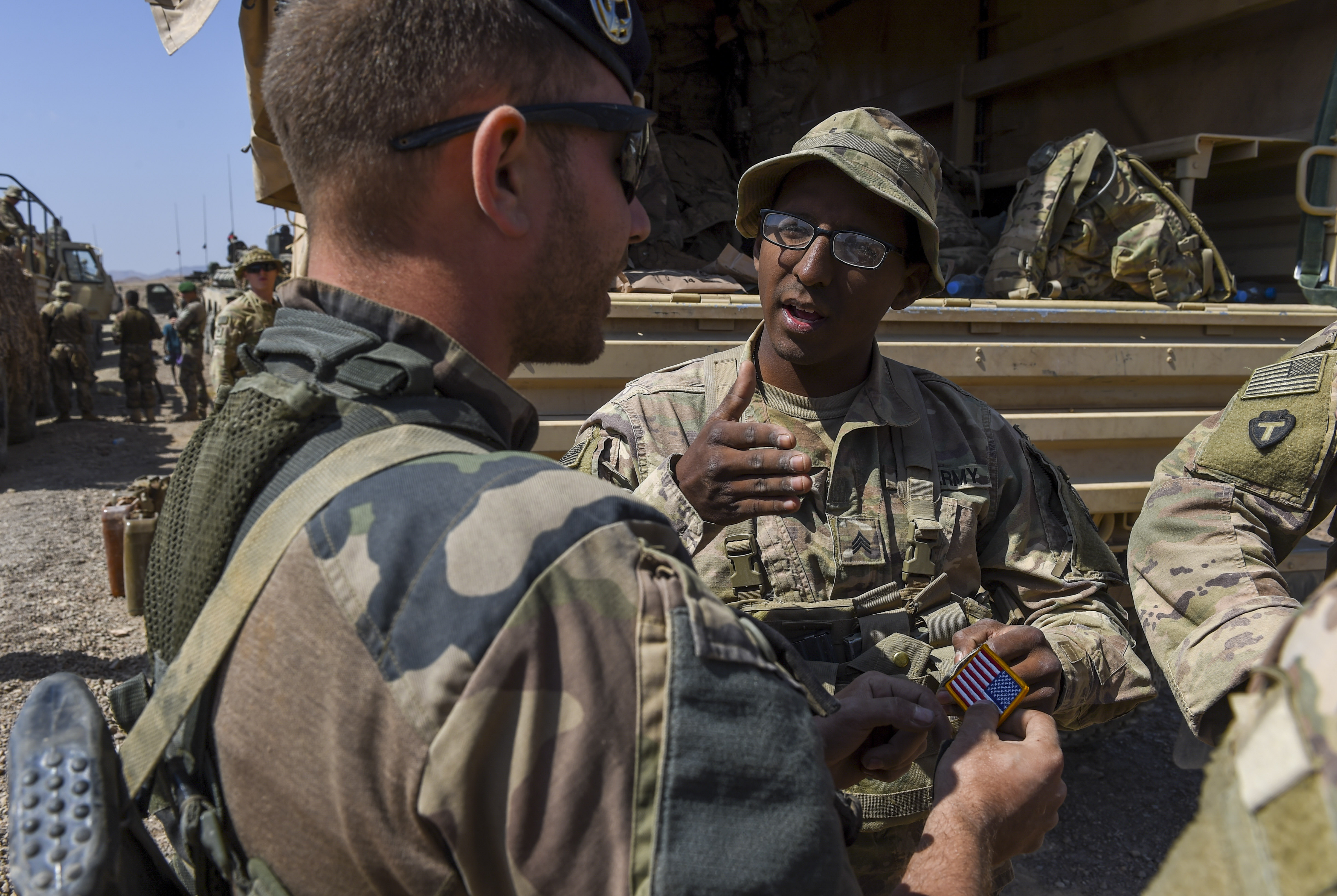 U.S. Army Sgt. Able Ballejo (right), assigned to 3rd Battalion, 144th Infantry Regiment, Texas Army National Guard, explains why the U.S. flag appears backwards on a traded patch to a French marine after the graduation ceremony of a French Desert Commando Course near Ali Sabieh, Djibouti, Dec. 7, 2017. U.S. service members assigned to Combined Joint Task Force - Horn of Africa participated in the 12-day course, in which they learned the fundamentals of desert combat, survival, and troop movements while also bridging language and cultural barriers between French and American troops. (U.S. Air Force photo by Staff Sgt. Timothy Moore)