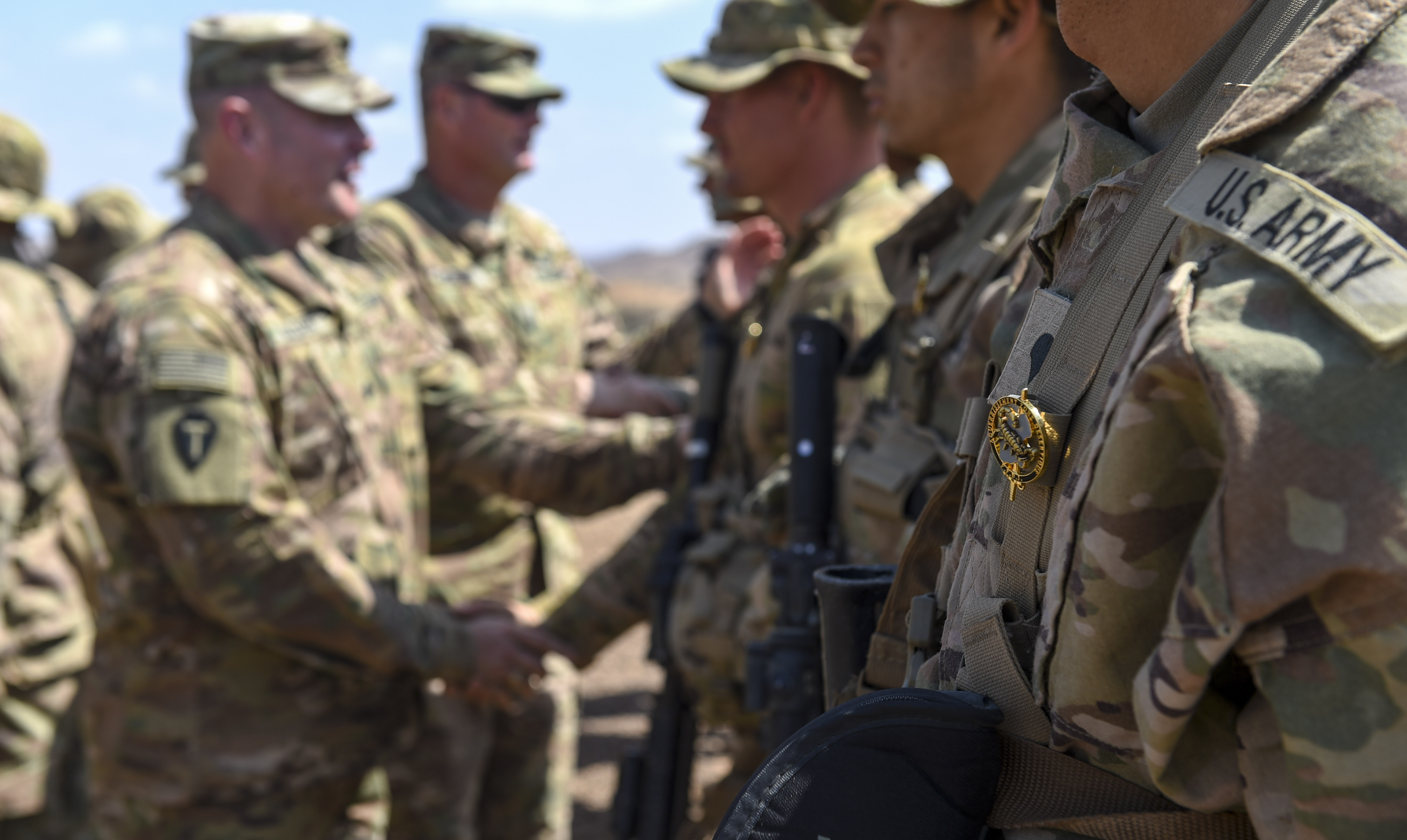 U.S. Army Lt. Col. Ross Walker, commander of 3rd Battalion, 144th Infantry Regiment, Task Force Bayonet, and Command Sgt. Maj. Clinton Petty, Task Force Bayonet command sergeant major, congratulate graduates of the French Desert Commando Course near Ali Sabieh, Djibouti, Dec. 7, 2017. U.S. service members assigned to Combined Joint Task Force - Horn of Africa participated in the 12-day course, in which they learned the fundamentals of desert combat, survival, and troop movements while also bridging language and cultural barriers between French and American troops. (U.S. Air Force photo by Staff Sgt. Timothy Moore)