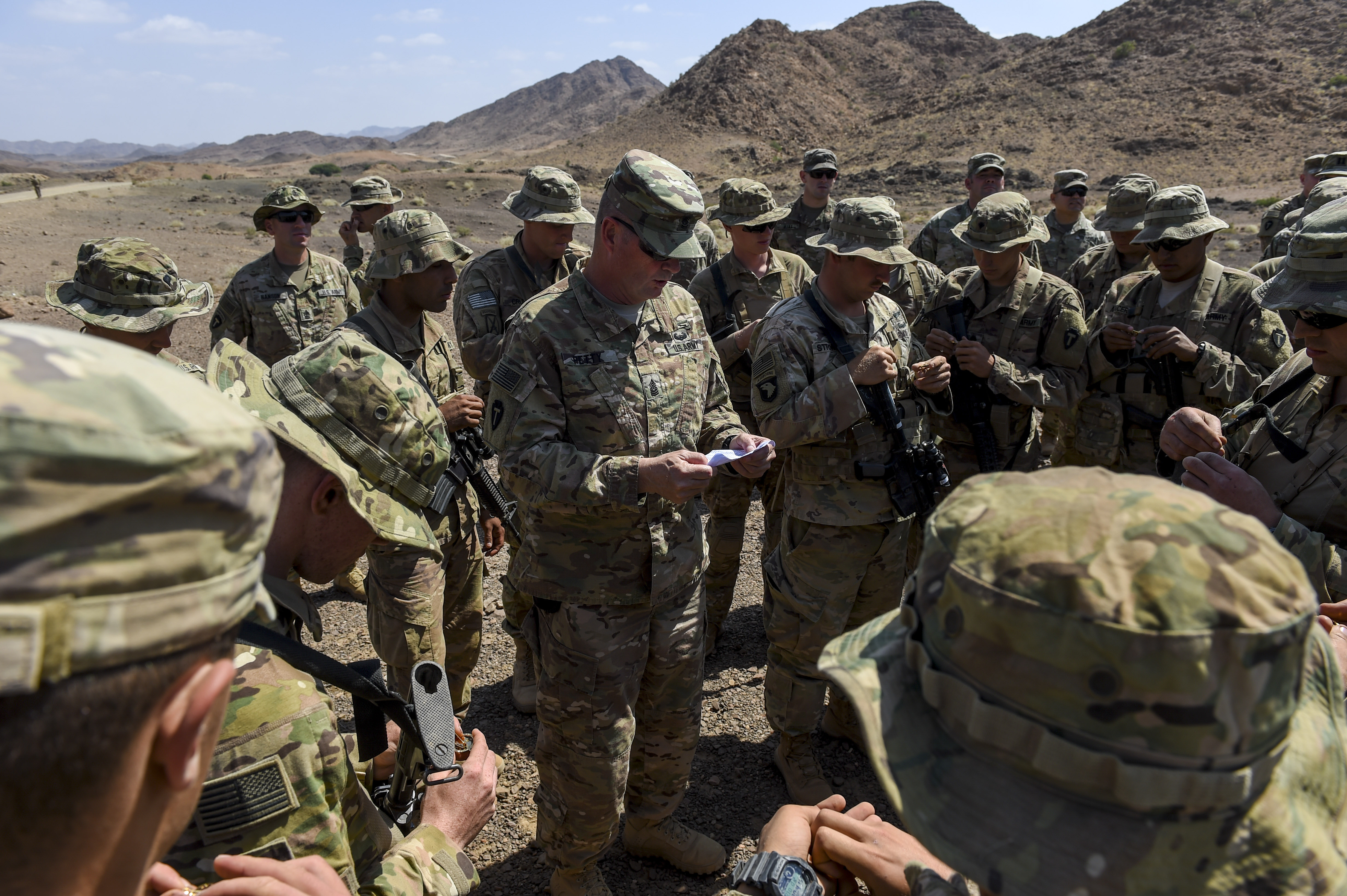 U.S. Army Command Sgt. Maj. Clinton Petty (center), command sergeant major of the 3rd Battalion, 144th Infantry Regiment, Task Force Bayonet, attached to Combined Joint Task Force - Horn of Africa (CJTF-HOA), calls out serial numbers for French Desert Commando Course pins after the course graduation ceremony near Ali Sabieh, Djibouti, Dec. 7, 2017. Each service member, all of whom are assigned to CJTF-HOA, received a pin that was specifically designated to him for graduating the 12-day course. During the course, they learned the fundamentals of desert combat, survival, and troop movements while also bridging language and cultural barriers between French and American troops. (U.S. Air Force photo by Staff Sgt. Timothy Moore)