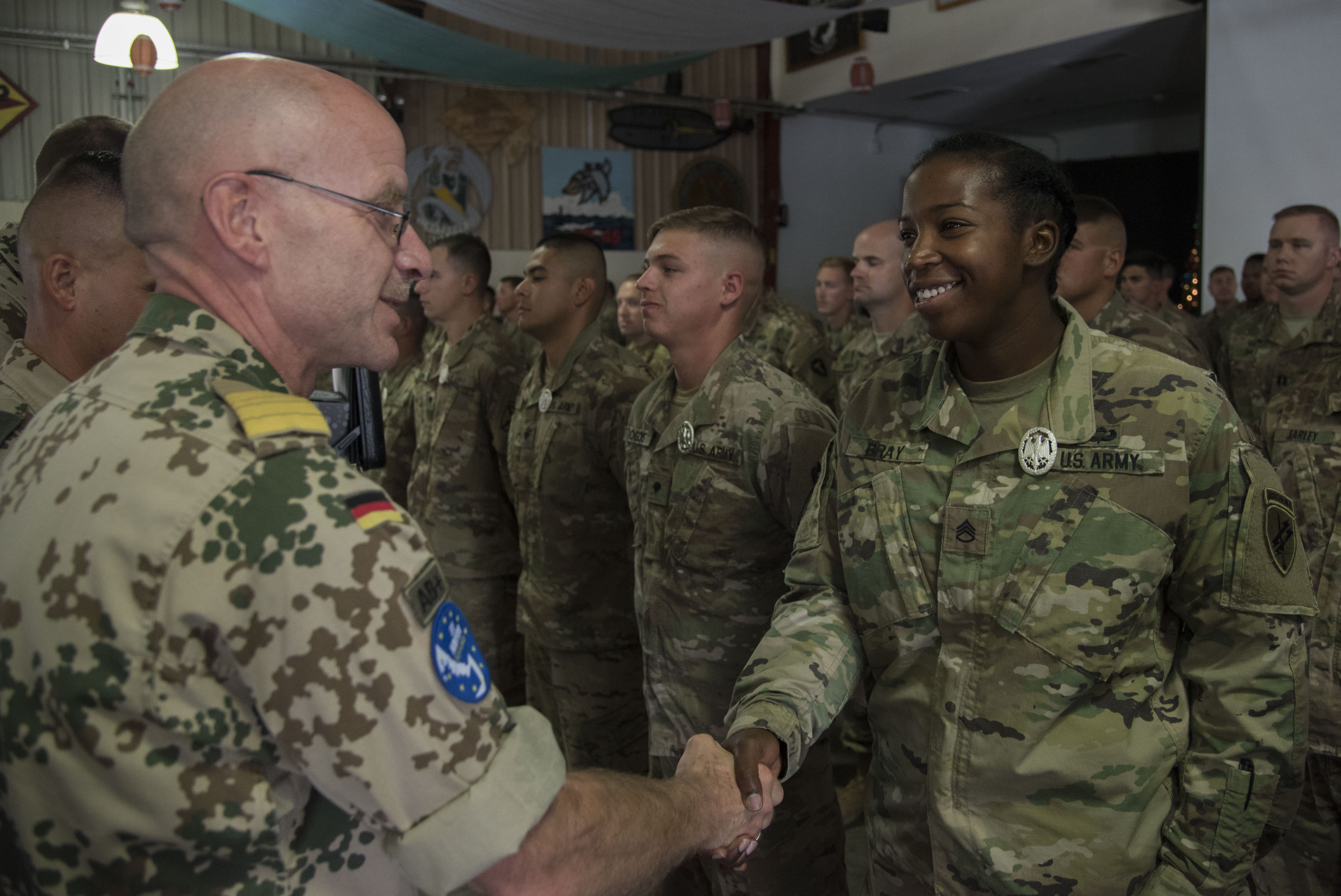 U.S. Army Staff Sgt. Sierra Bray, 346th Tactical Psychological Operations Company (Airborne), U.S. Army Reserve, Columbus, Ohio, deployed with Combined Joint Task Force-Horn of Africa, shakes hands with German commander Axel Schilling as she is awarded the German Armed Forces Proficiency Badge (GAFPB), a decoration of the Armed Forces of the Federal Republic of Germany, at Camp Lemonnier, Djibouti, Dec. 8, 2017. Competitors completed a physical fitness test, uniformed swim, weapons qualification, ruck march, first aid course and chemical warfare course to be awarded the GAFPB, one of the few foreign allied military awards that U.S. service members are authorized to wear. (U.S. Air National Guard photo by Staff Sgt. Allyson L. Manners)